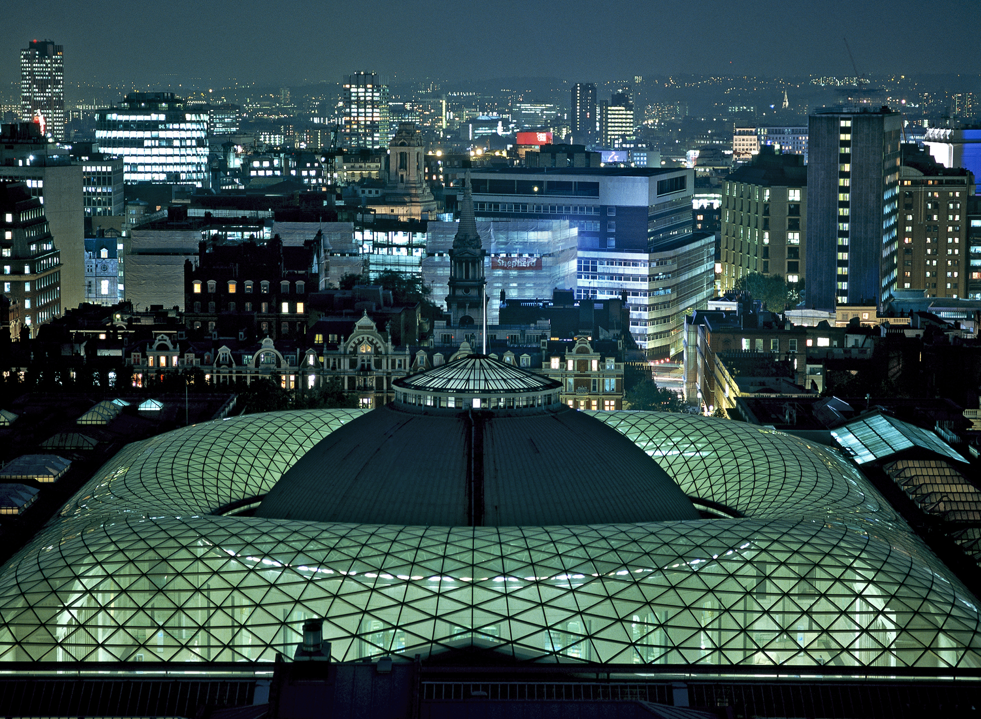 A photograph of the Great Court at night taken from above, illuminated in green from the inside, with the skyline of London lit up in the background.