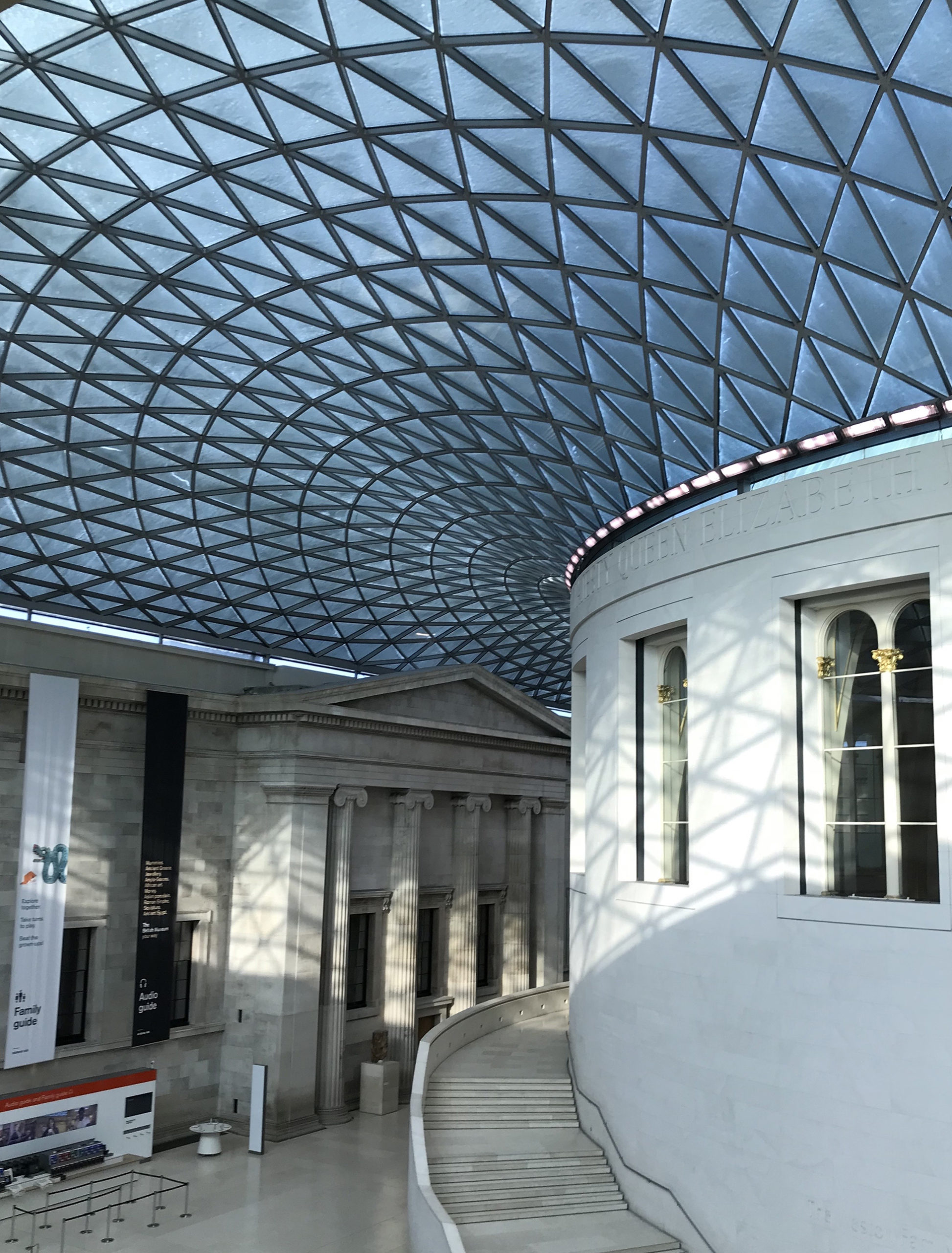 Snow which has settled on the glass panels of the Great Court, making them dark and patchy, and the floodlights encircling with Round Reading Room shining onto the space below.