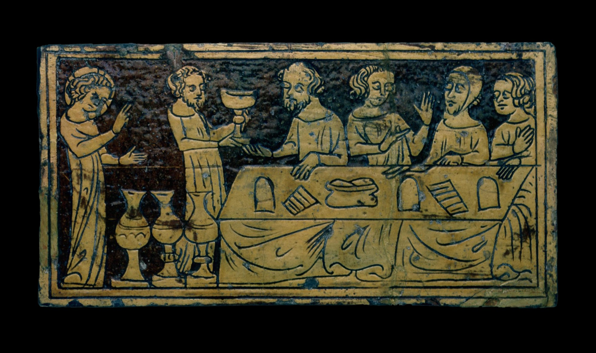 Earthenware tile. The tile has a dark background with figures shown in a cream slip. The tile shows a group of people sitting around a table. A standing figure holds a large cup. A figure with a halo stands apart from the party on the far left and raises his hands.