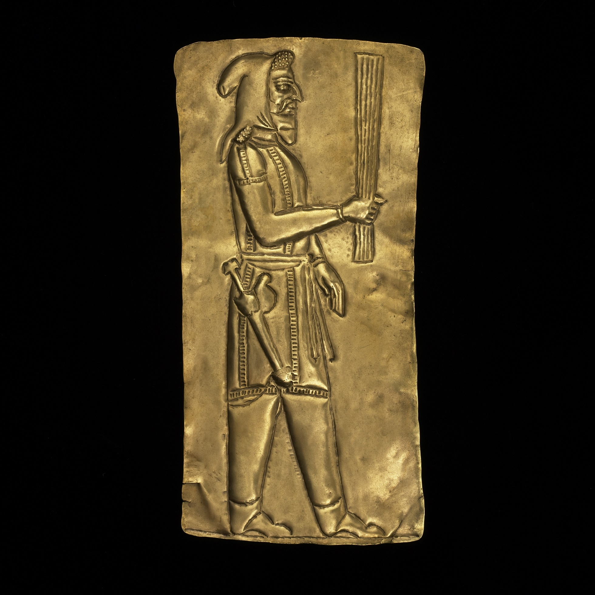 Rectangular gold plaque embossed with male figure facing right, wearing a belted tunic