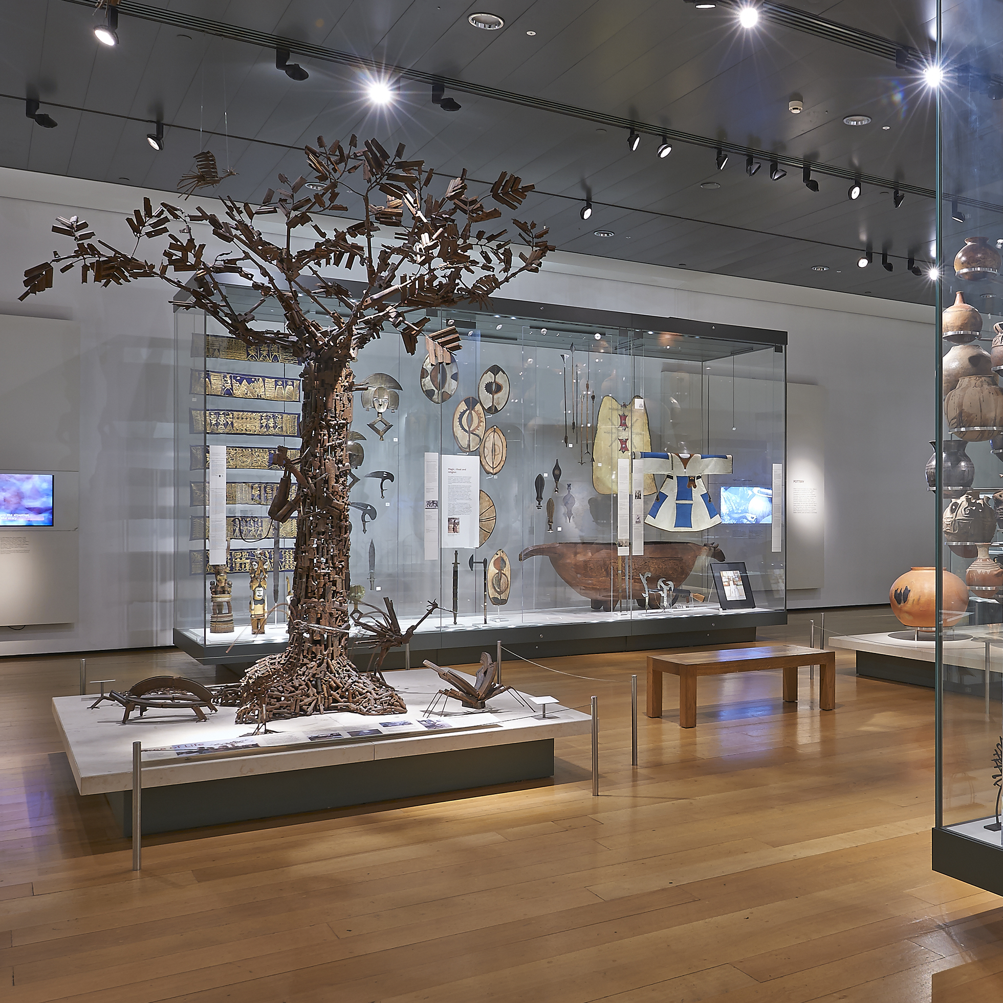 A photograph of Room 25 of the Museum, showing display cases filled with African objects, and the Tree of Life on a plinth in the centre of the Room.