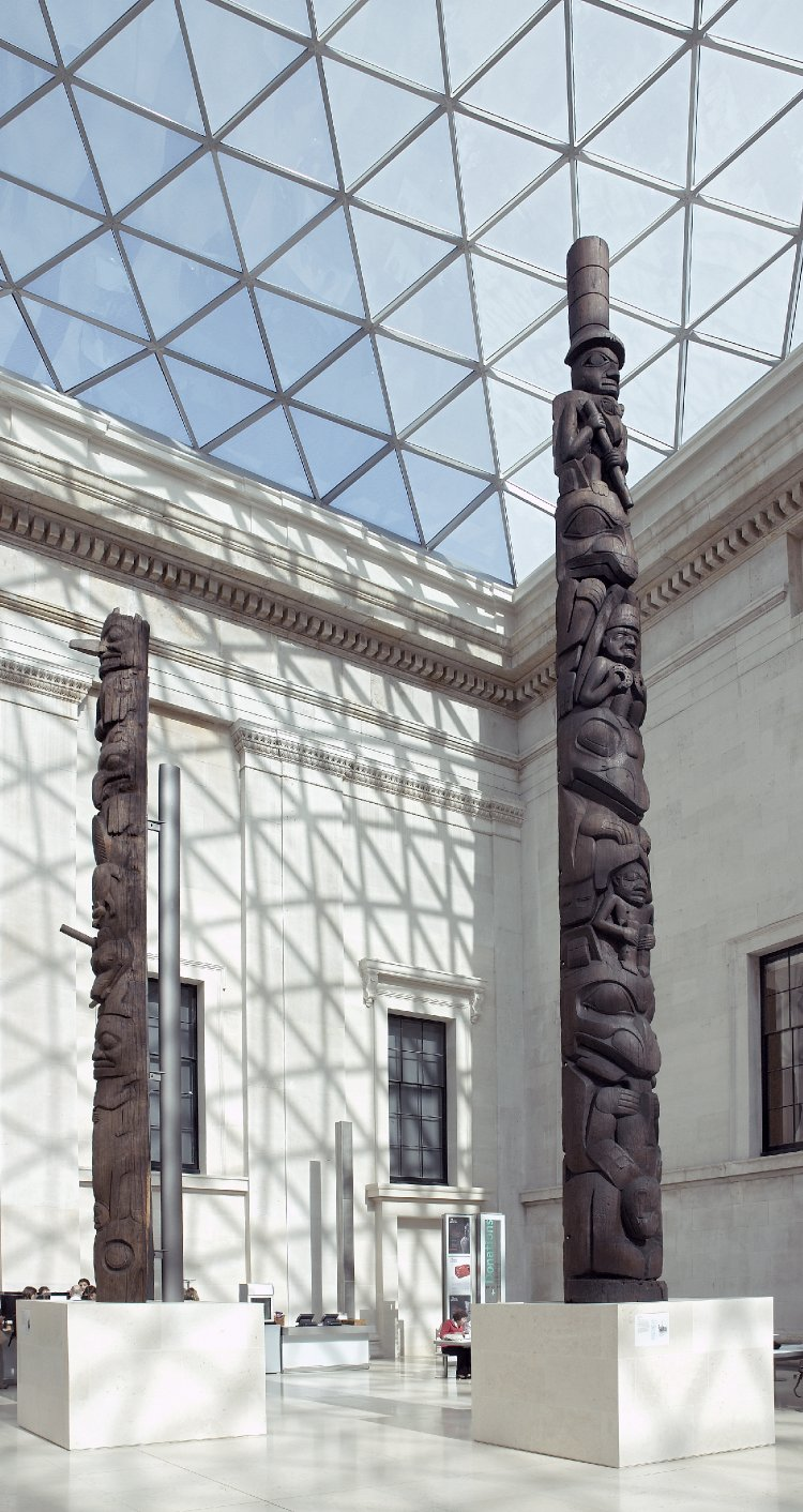 Two dark brown wooden totem poles, standing on plinths in the corner of the Great Court, rising up towards the glass roof above.