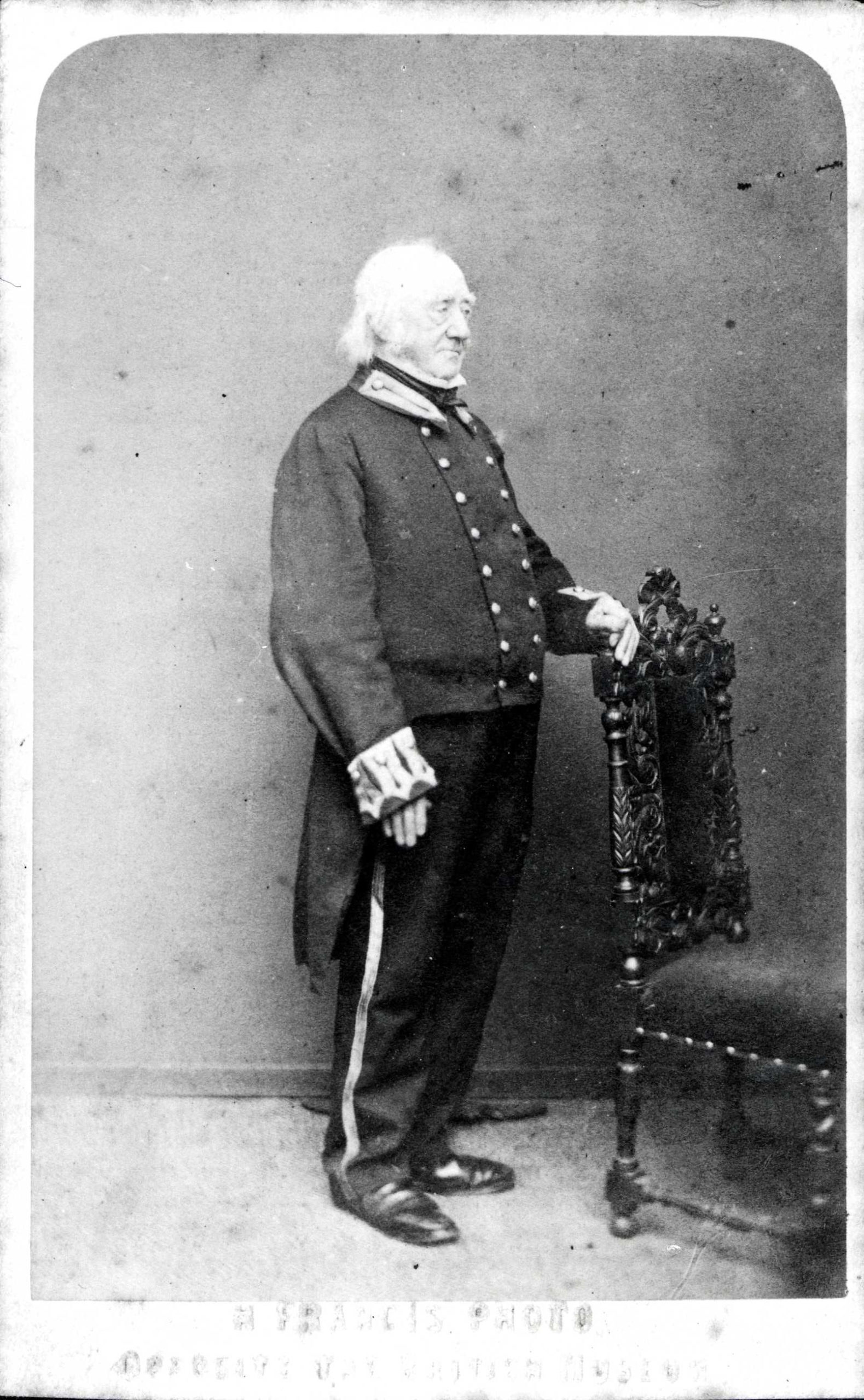 A black-and-white photograph of n elderly man wearing the Windsor Livery - a formal double-breasted jacket with tails, embroidered collar, shiny shoes, and trousers with piping down the sides.