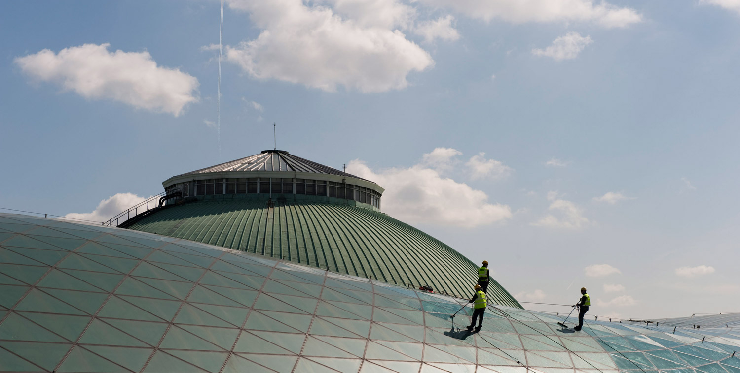 Three cleaners attached to a network of cables to the Great Court, wearing high-vis clothing, cleaning the glass with water and brushes.