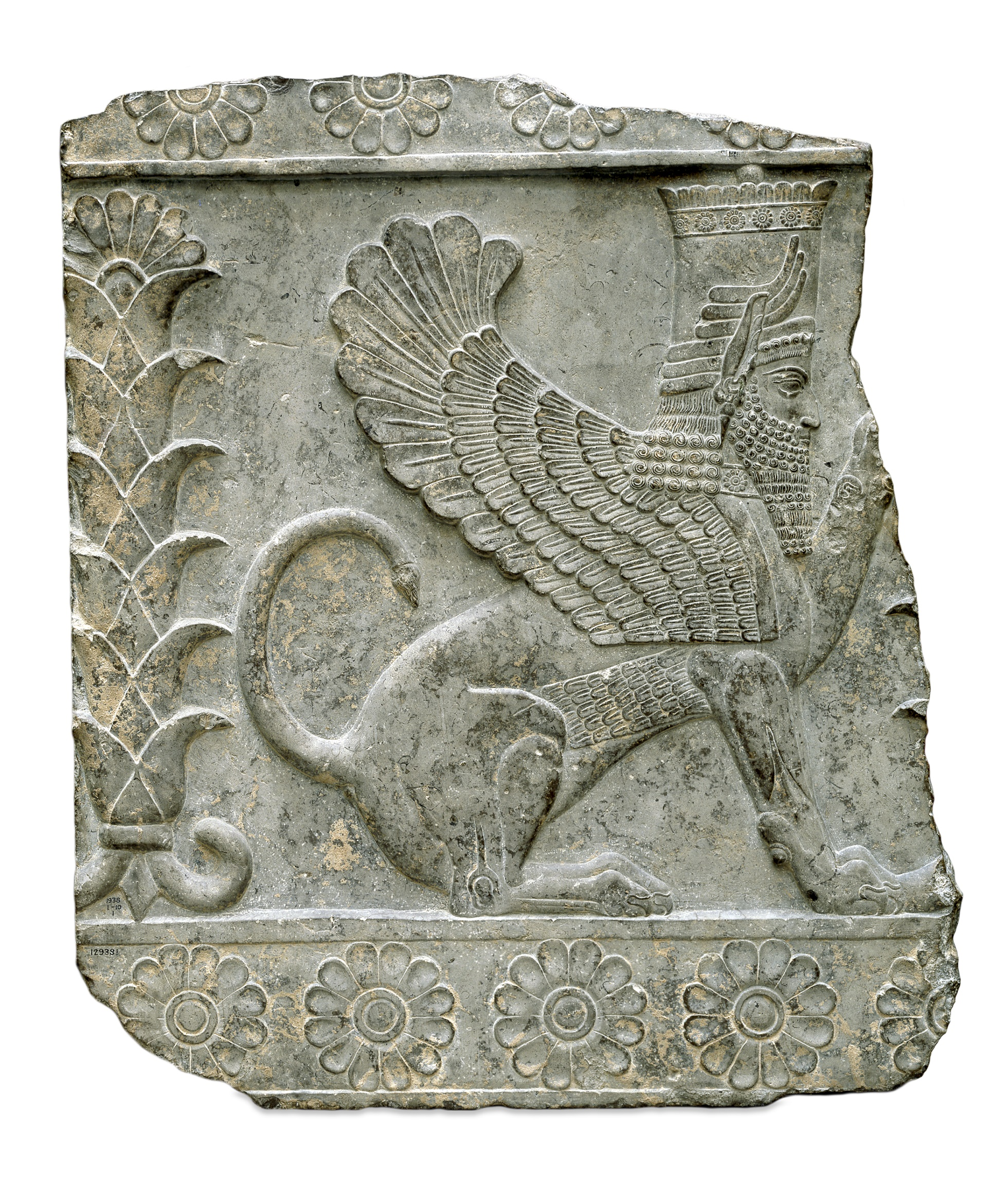 Relief showing a seated bearded male sphinx facing right with raised left forepaw, wearing divine horned head-dress with band of rosettes below the feathered top