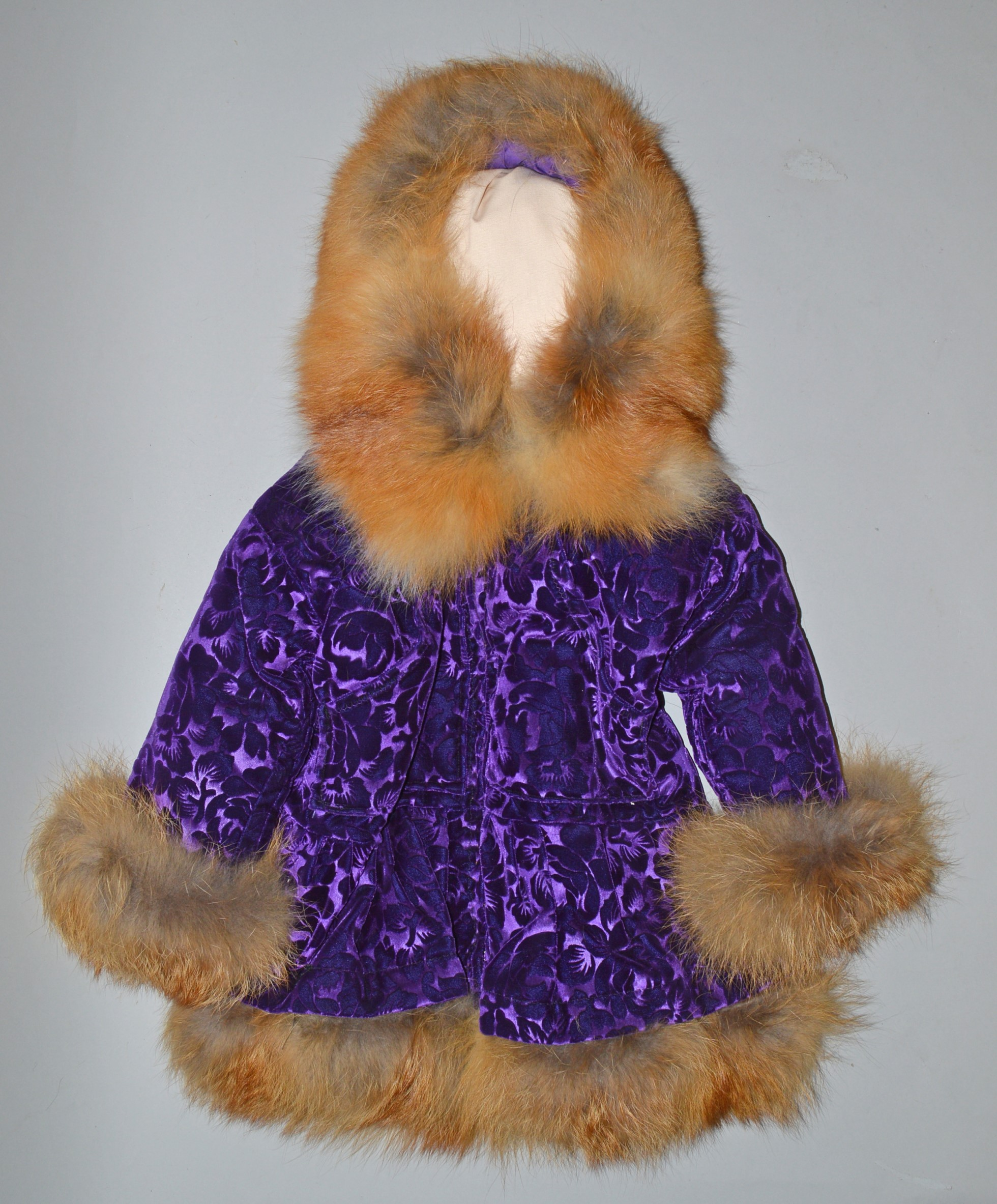 Child's parka made of purple velveteen, mauve with a red fox trim on the hood, cuffs and bottom of the jacket.