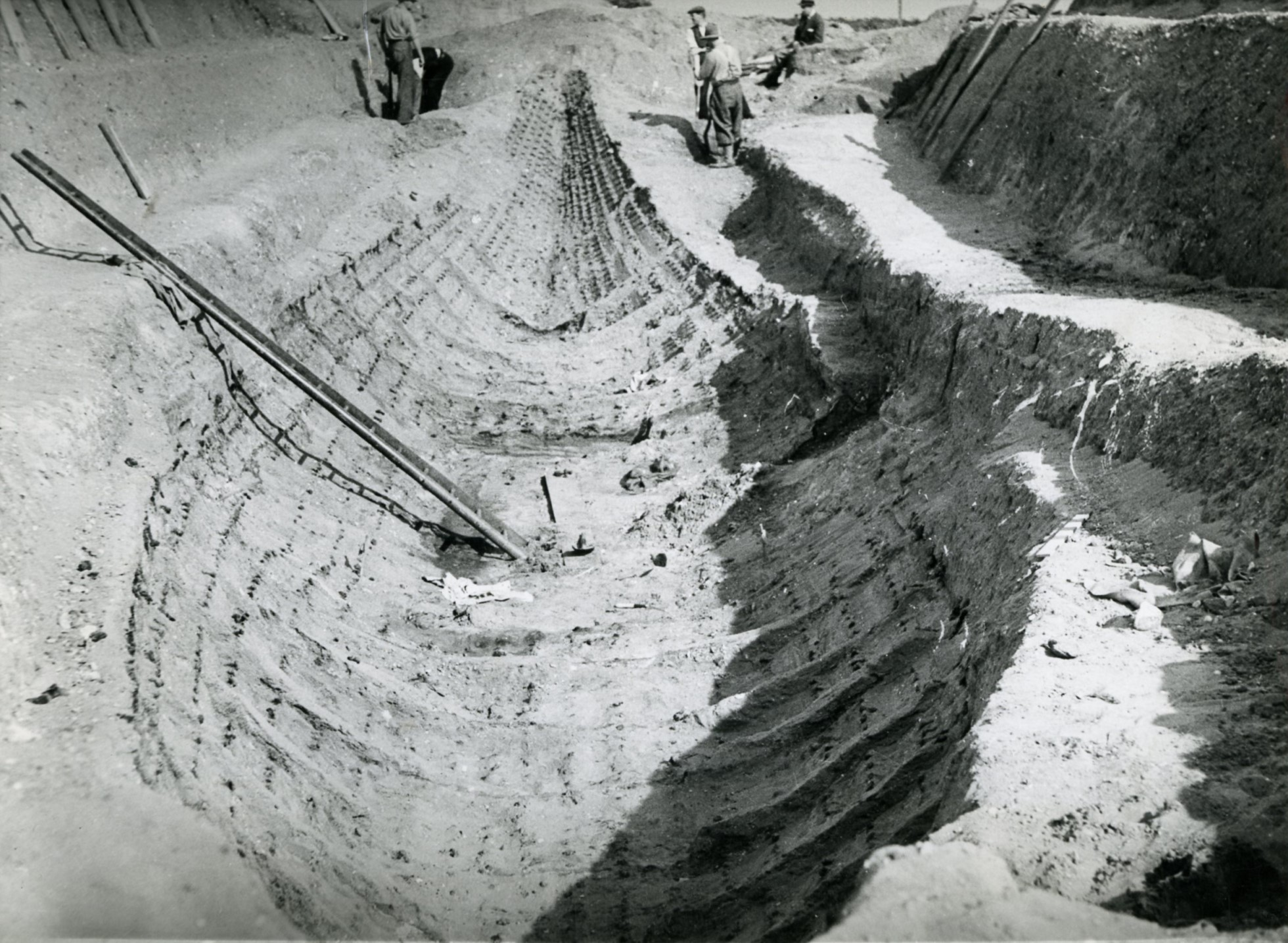Imprint of a large ship being excavated. A ladder is on the right providing access down into the ship trench. A bank can be seen on the right side.