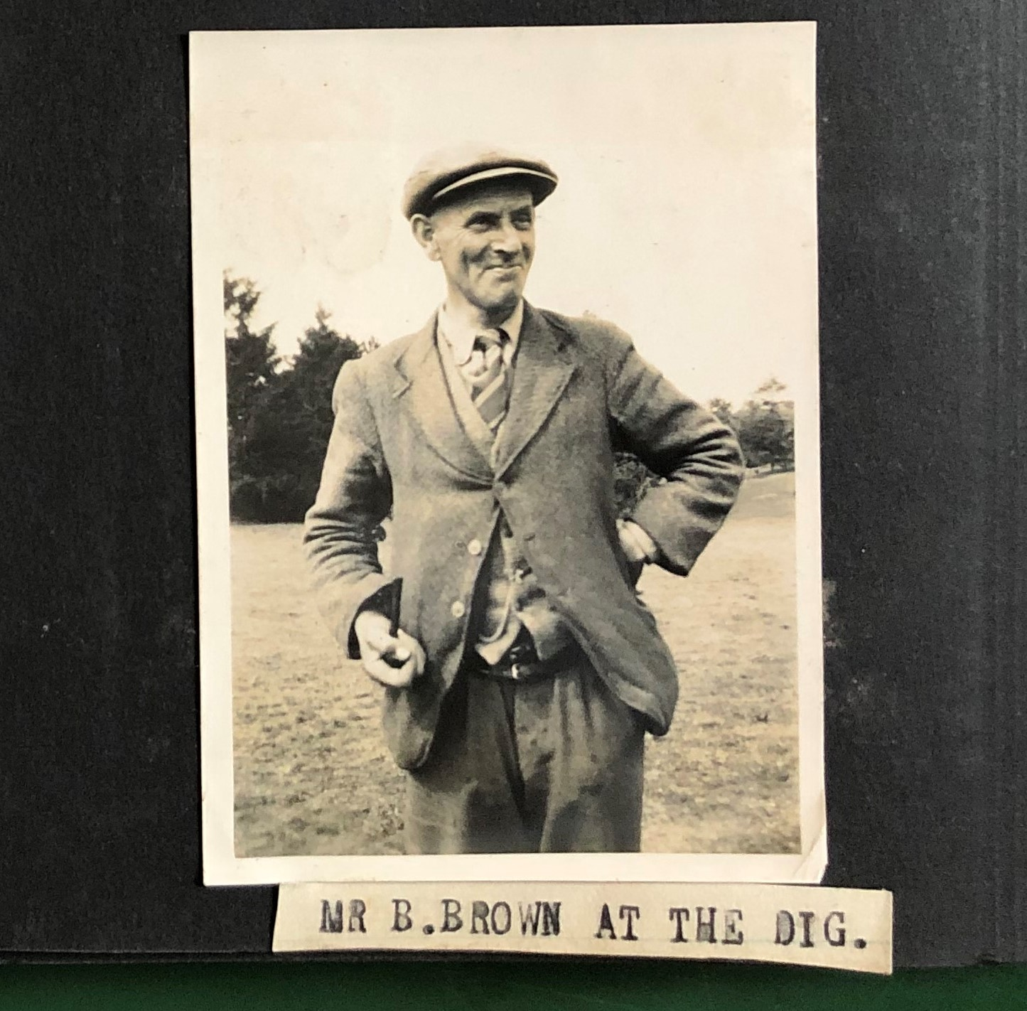 A black and white photograph of  Basil Brown wearing a slightly scruffy three piece suit and striped tie. He wear a flat cap and has his hand on his left hip. He smiles. Underneath the photo is a small piece of paper which reads, in type written in capitals 'Mr B. Brown at the Dig'.