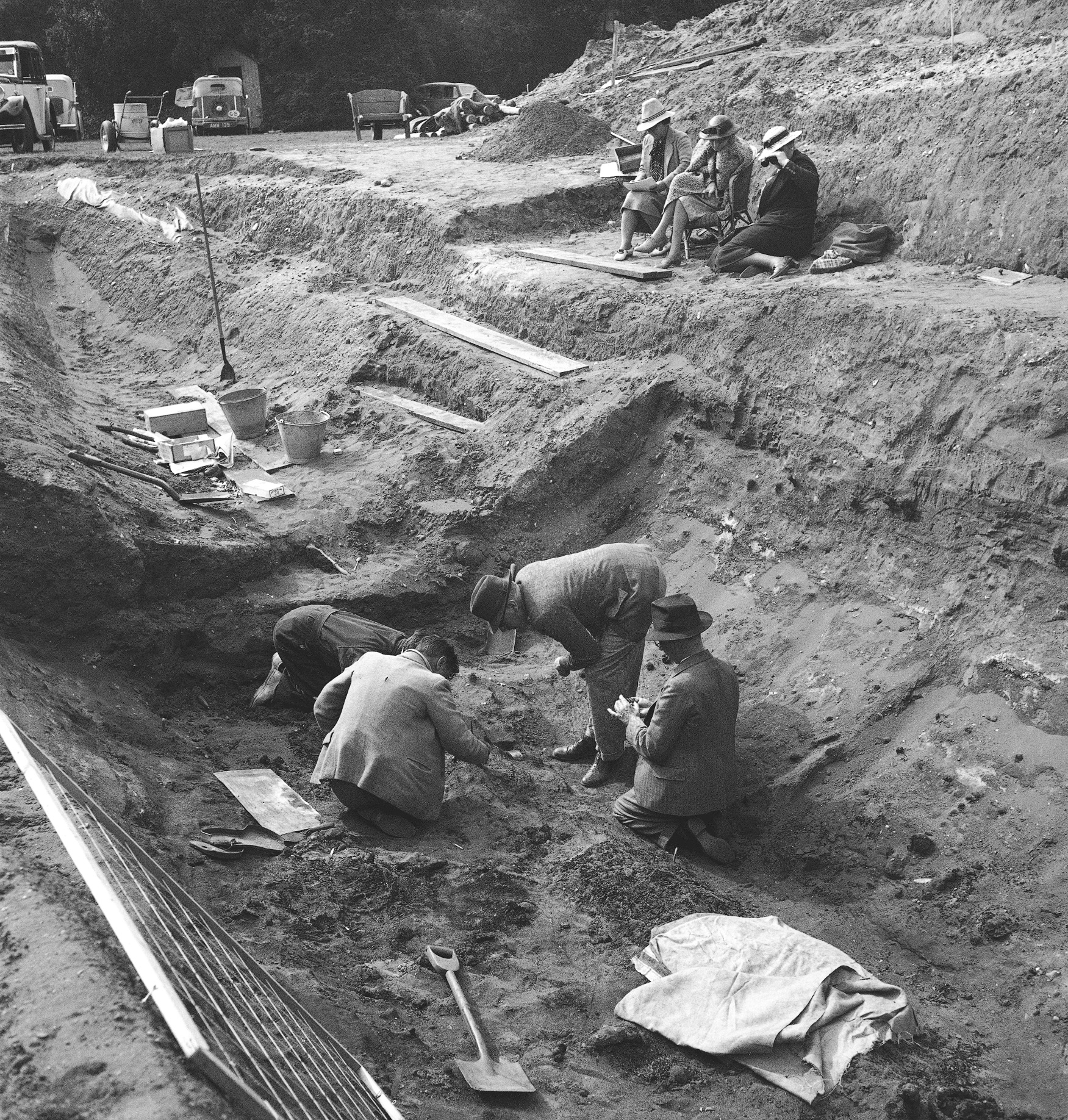 A black and white photo of men excavating in a trench. There is a sheet and a shovel in the trench. The men all wear jackets, trousers and hats. Three people sit at the top of the trench, two are seated on chairs one sits on the ground. There are vehicles in the background.
