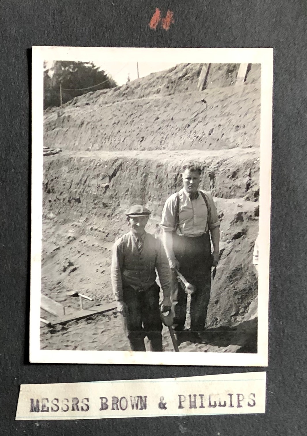 Black and white photo showing two men - Basil brown on the left and Charles W. Philips on the right. They are stood in a large trench. Basil Brown wears a shirt, trousers, waistcoat and flat cap. H ehas his hand on a handle of what looks like a shovel. Charles W. Philips stands slightly above Basil Brown and wears a shirt, trousers and braces and holds a trowel.