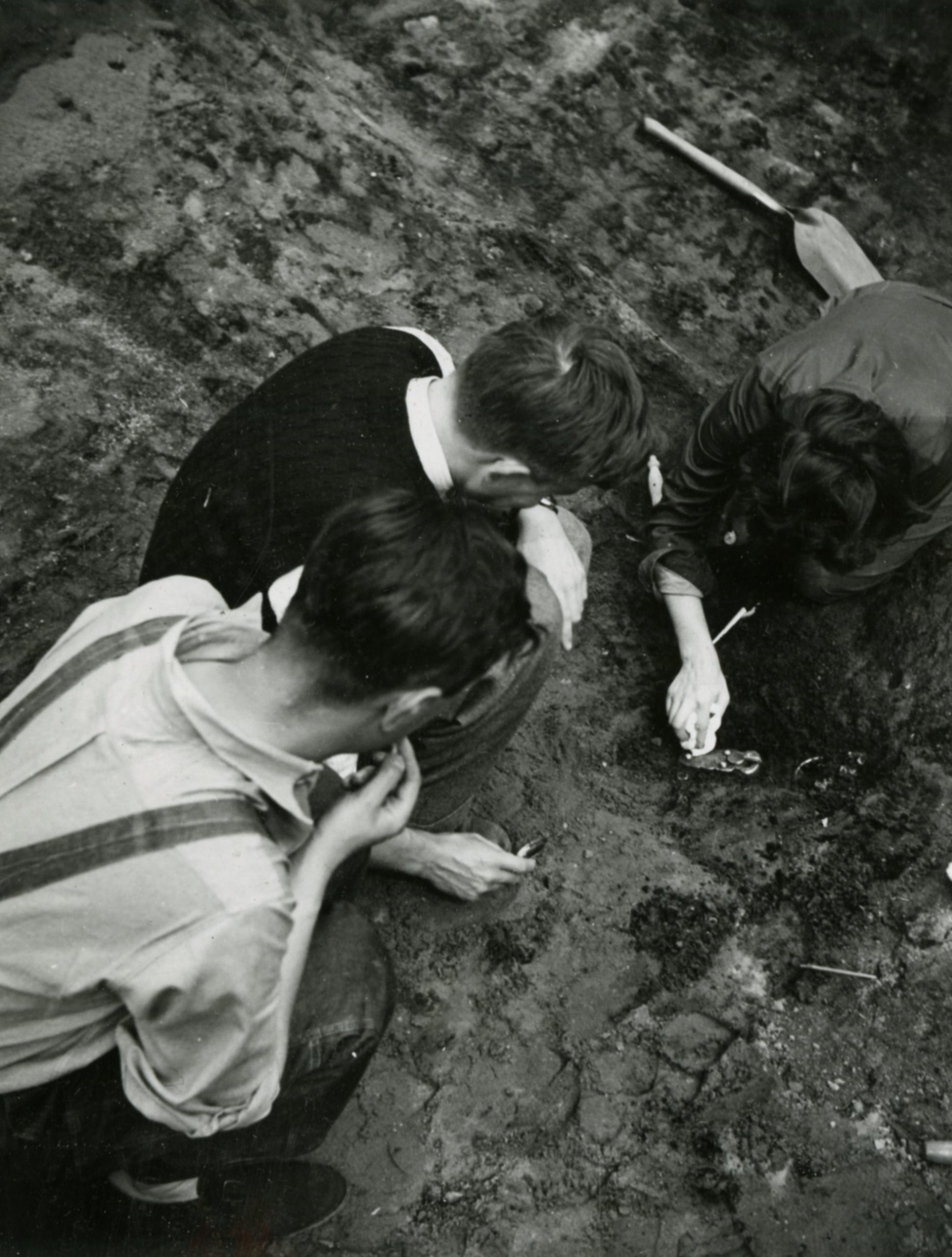 View from above of three people excavating in a trench. We see the backs of their heads as they work. One of them is digging around a gold object.