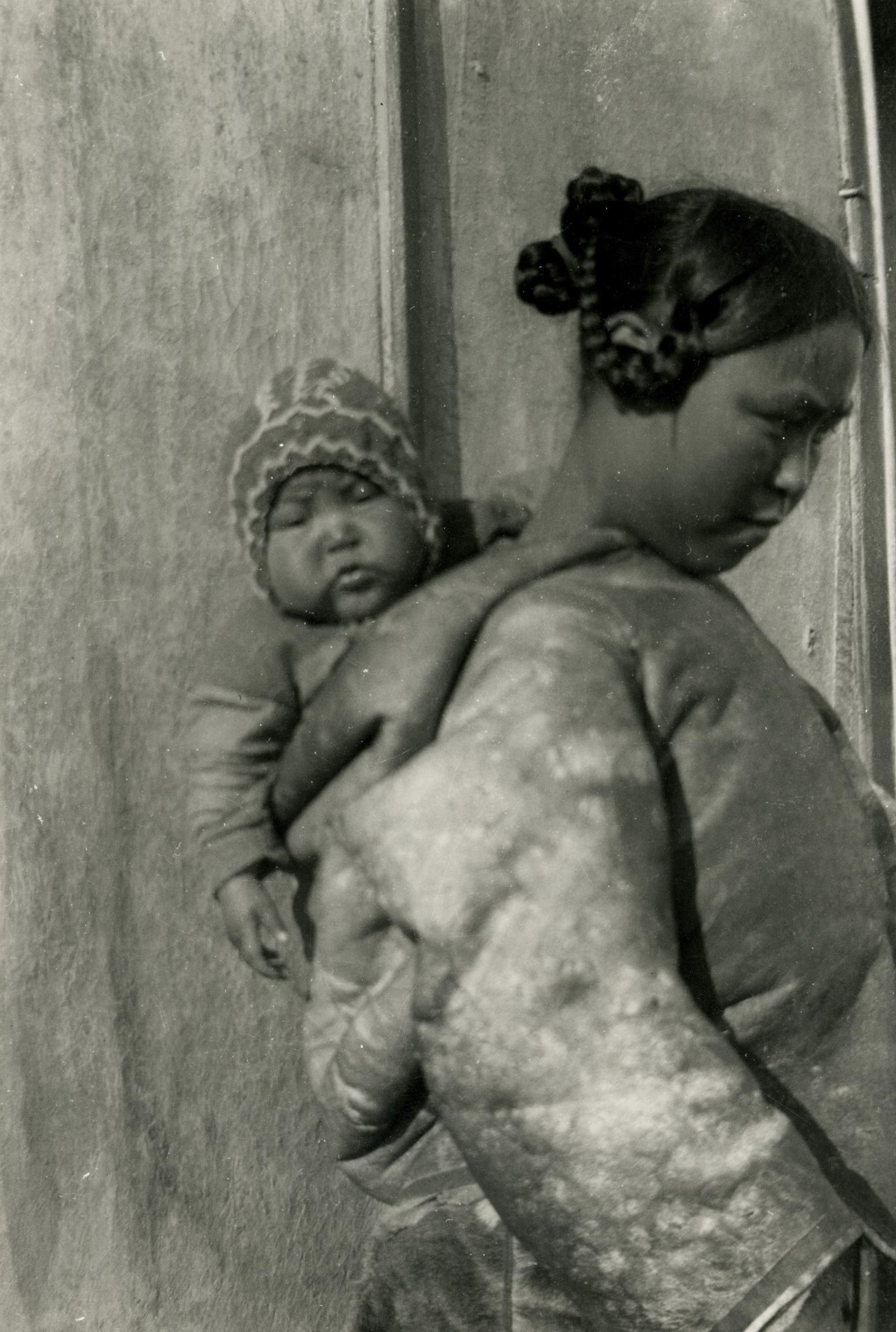 A black and white photograph showing a woman carrying a baby in her amautis. The woman is shown in profile, turned to the right . She wears a thick coat and has braided hair. Her baby is seen in the hood, facing the viewer, and wears a coat and hat.