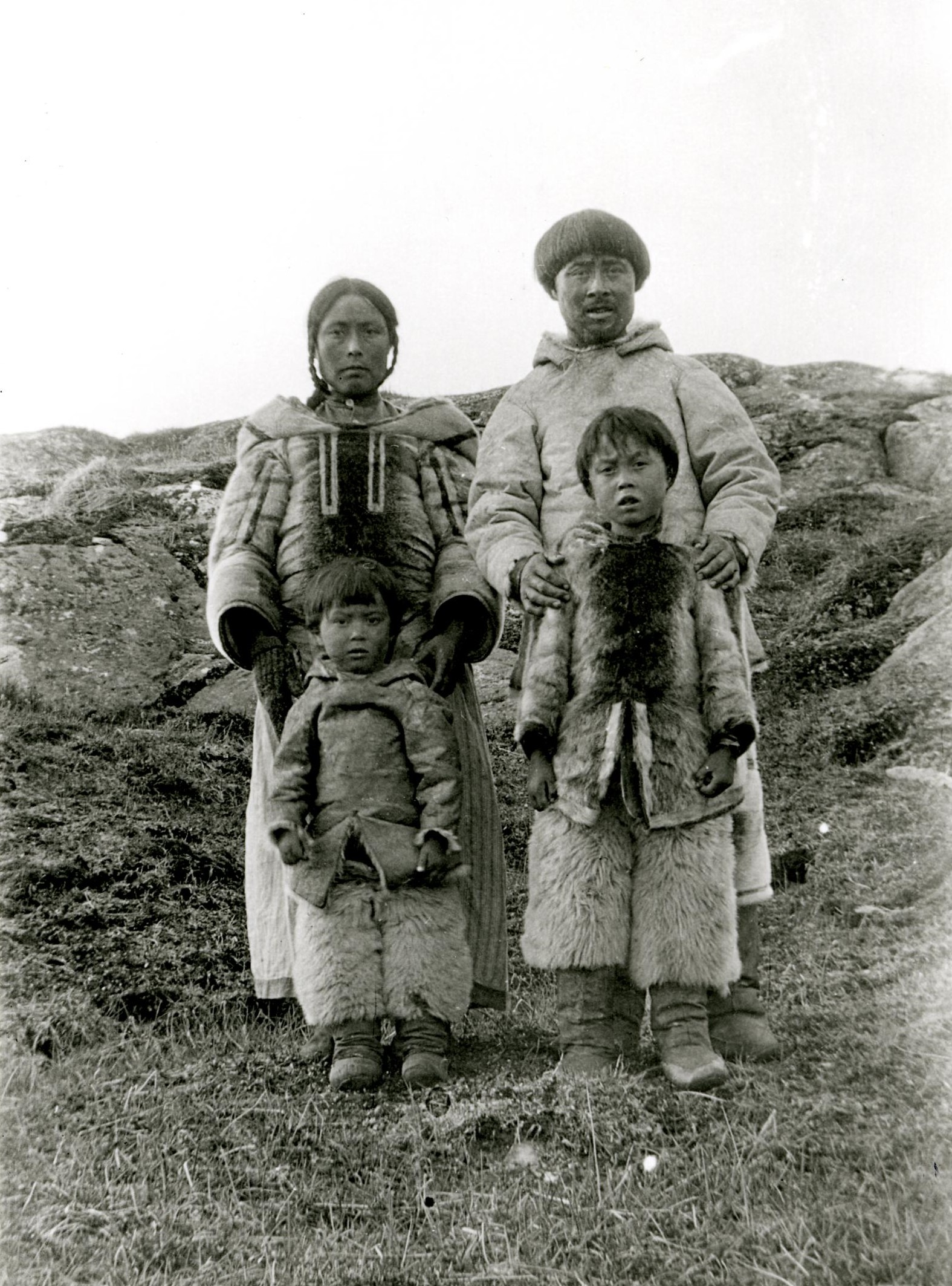 Black and white photograph of an Inuit man, woman, and two children standing outdoors. The woman wears sections of her hair in plaits and tied back, a parka, and a long skirt. The man wears a parka, trousers, and boots. Both children stand in front of the adults, and wear fur parkas, trousers, and boots.