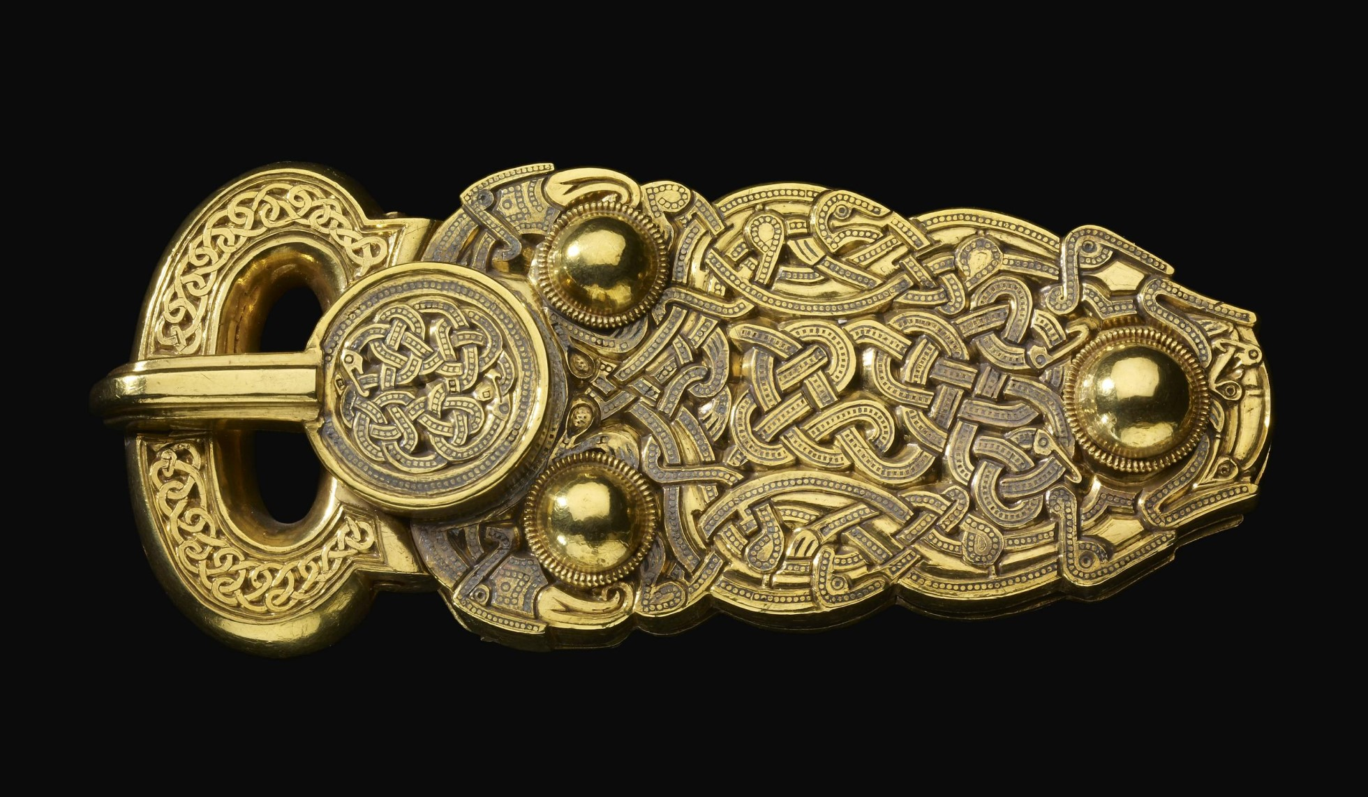 Gold belt-buckle. The upper surface is covered entirely with zoomorphic interlace, the design picked out in tiny punched circles and inlaid (except on the loop).