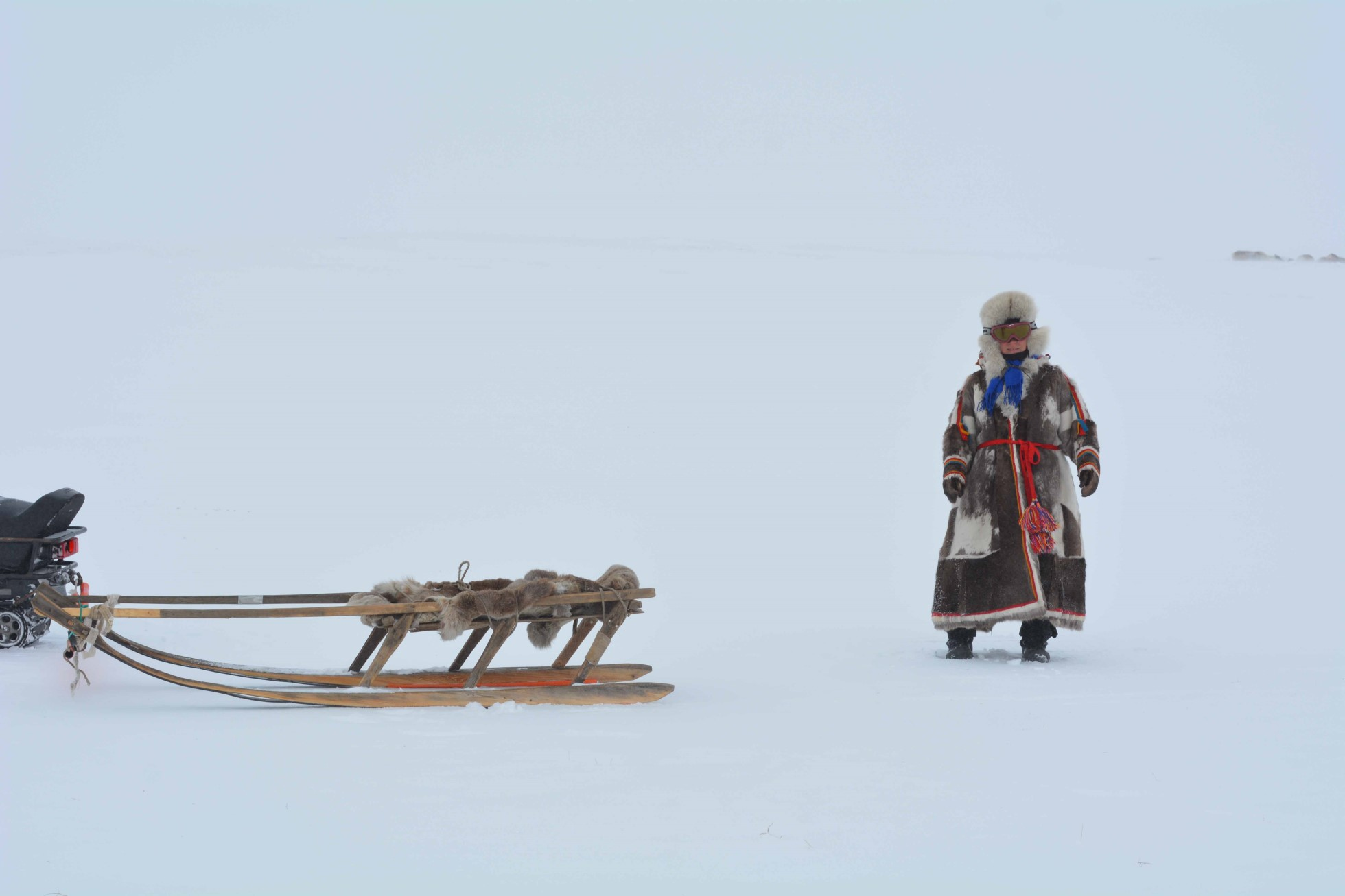 A photograph of a woman standing in the snow wearing a long fur parka and hat. The parka is brown with white decorations and a red belt. On the left is a wooden sled.