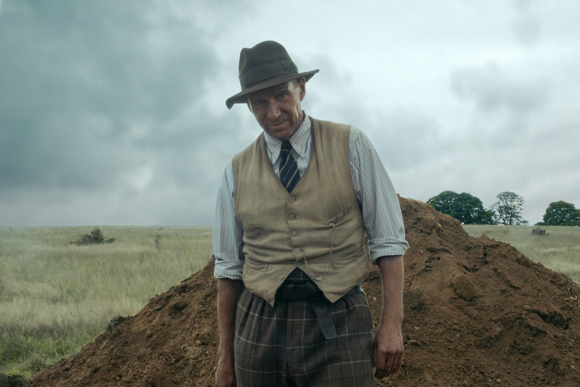 Photograph still from the film. The character of Basil Brown, played by Ralph Fiennes, stands in front of a large mound of soil. He wears brown check trousers, a cream waistcoat, blue shirt with the sleeves rolled up, a striped tie and brown hat. Behind him is a field of long glass and the sky is grey.