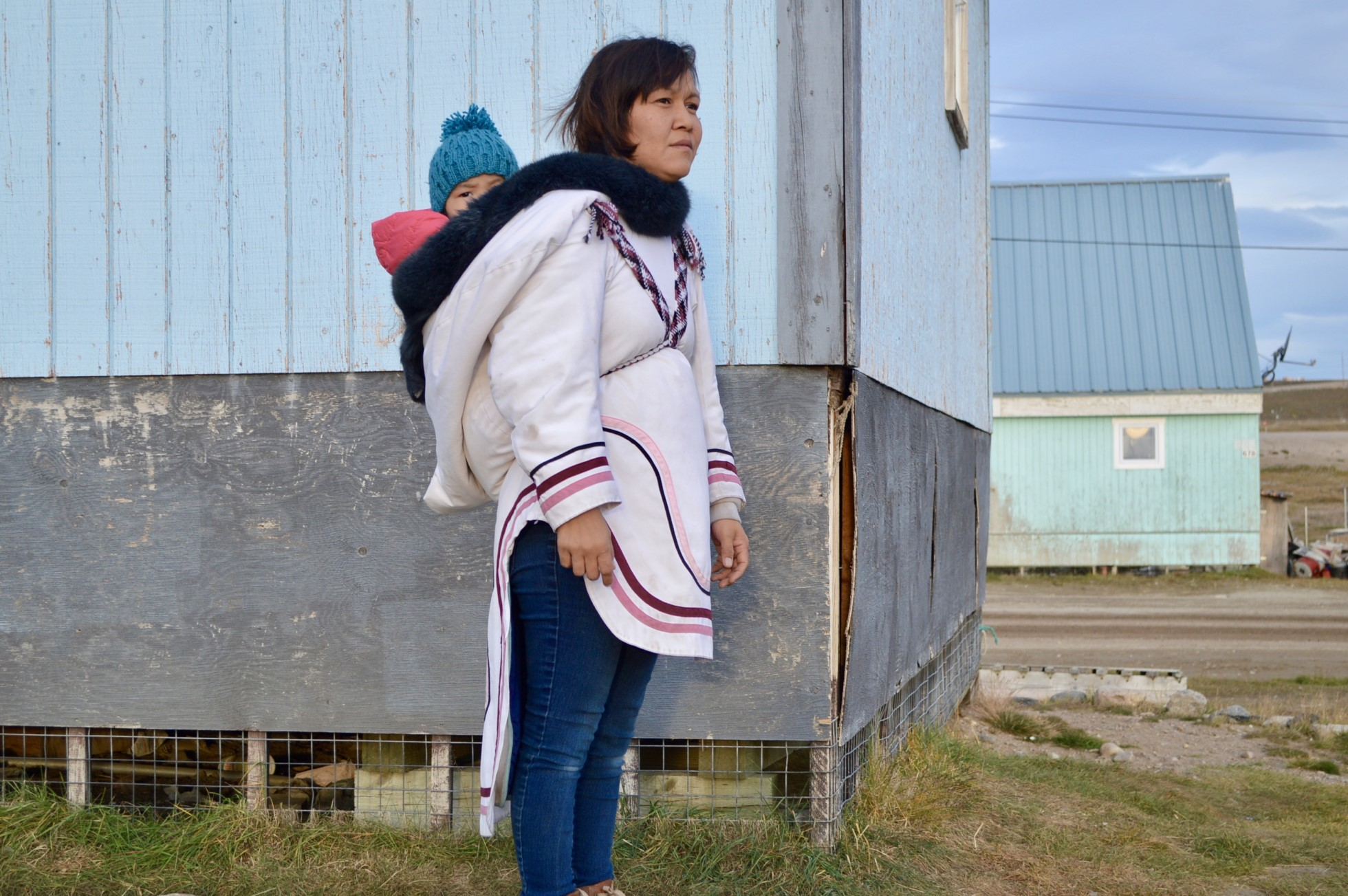 A woman is dressed in a amaut parka, carrying her child in a hood-like pocket on the back. The parka is made of off-white material with pink and purple trimming.