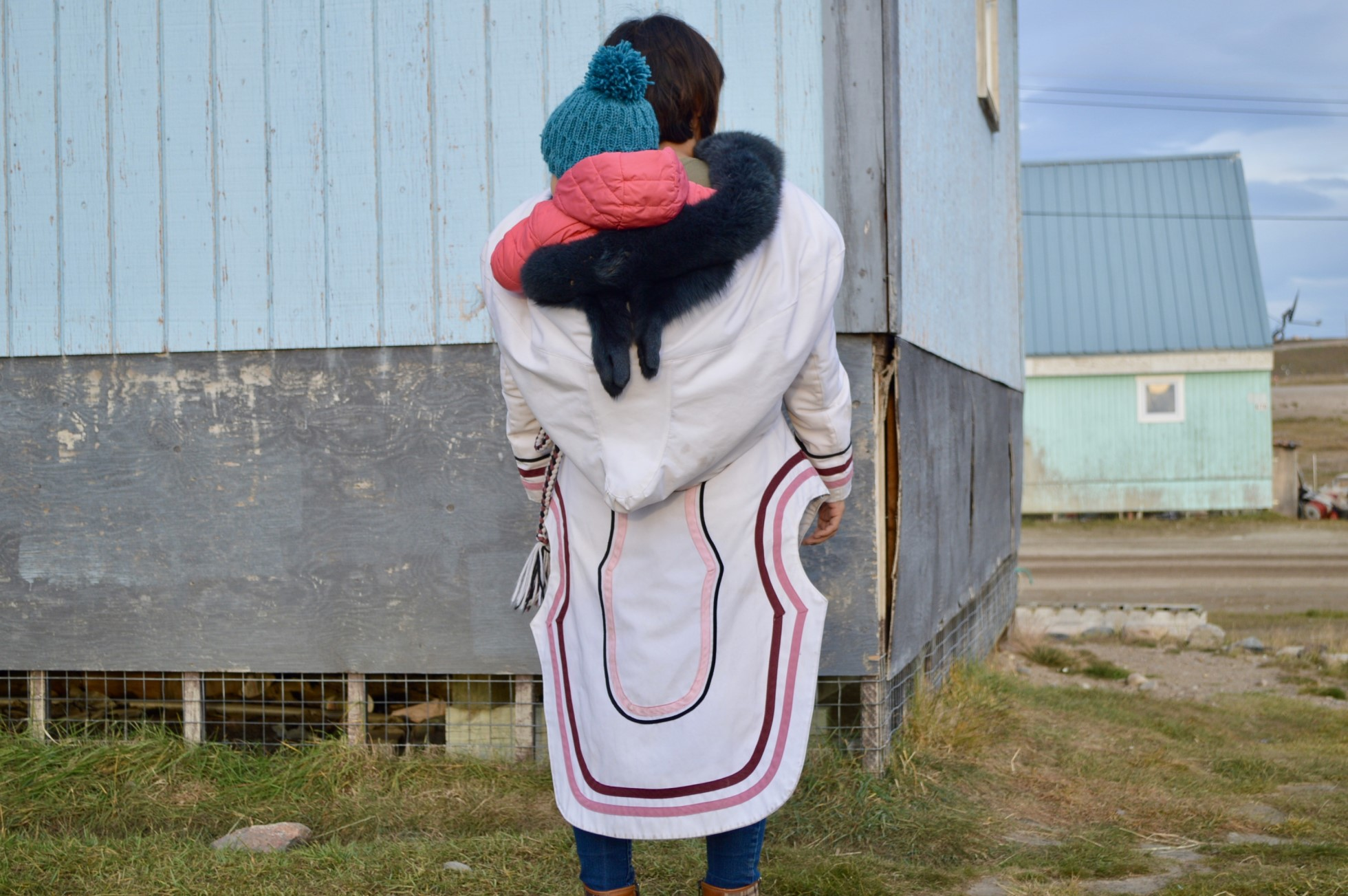 A photo of Sheila Katsak. She is photographed from behind, demonstrating how to wear the amautis parka. The child is shown in the pocket on the back. The back of the amautis drops down to the back of the calf. The amautis is white with purple and pink trimming.