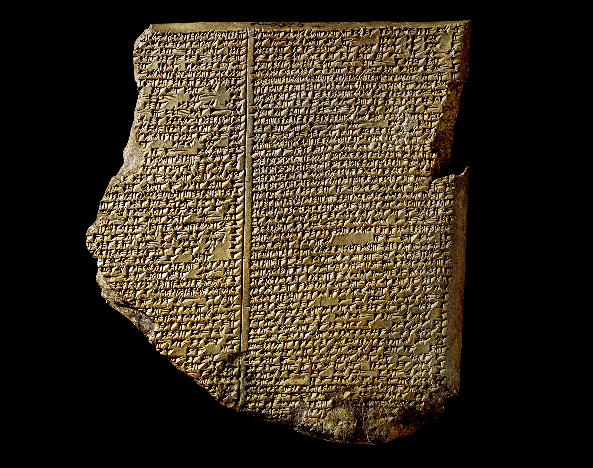 A mid-brown rectangular clay tablet covered with cuneiform script written in two columns, telling the story of the epic of gilgamesh.