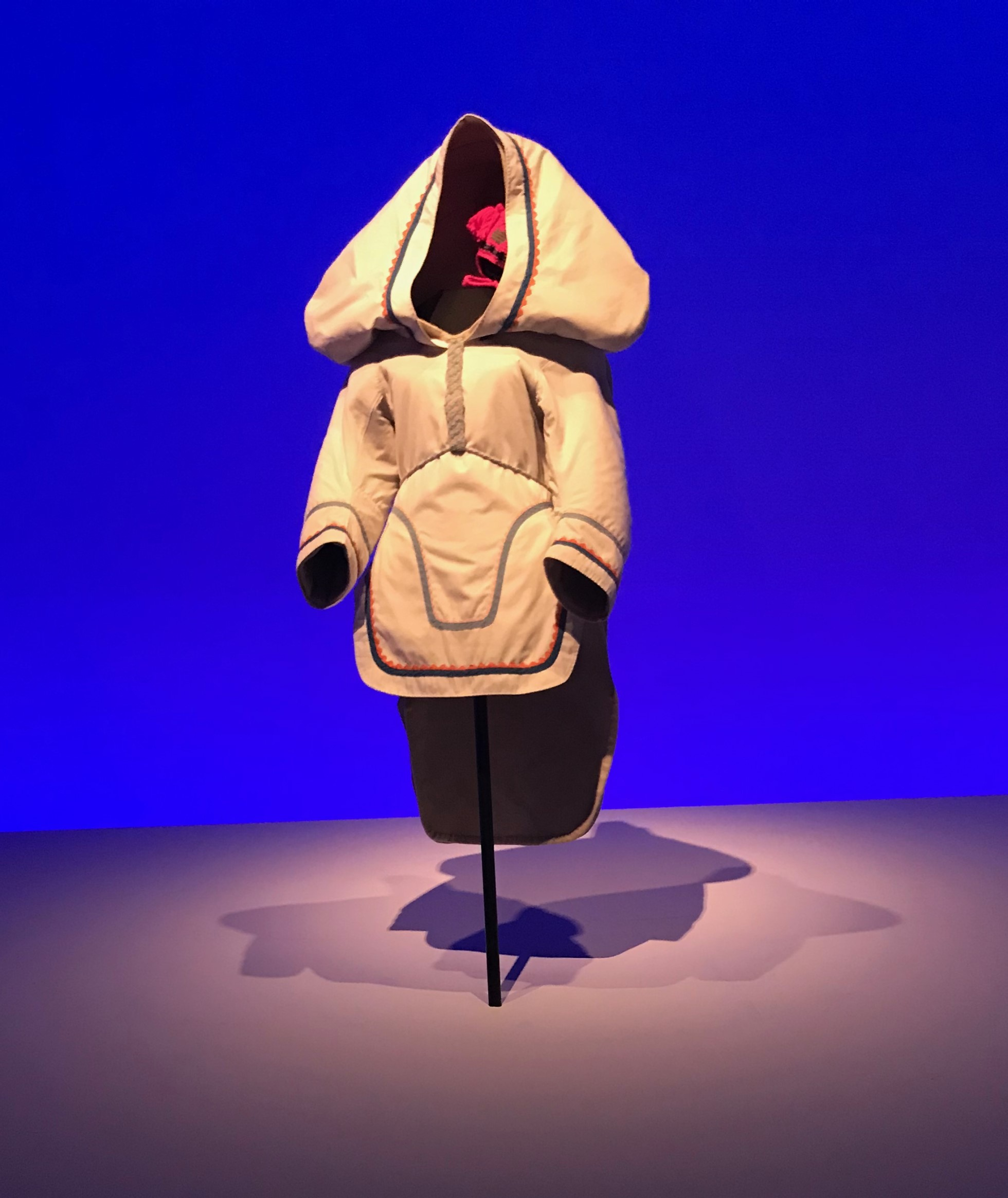 Photograph of an amauti parka in the exhibition. The amautis is a cream or off white. It has the characteristic large hood and tail at the back.  There is dramatic lighting in the exhibition with a dark blue colour to the wall in the background. There are strong shadows.