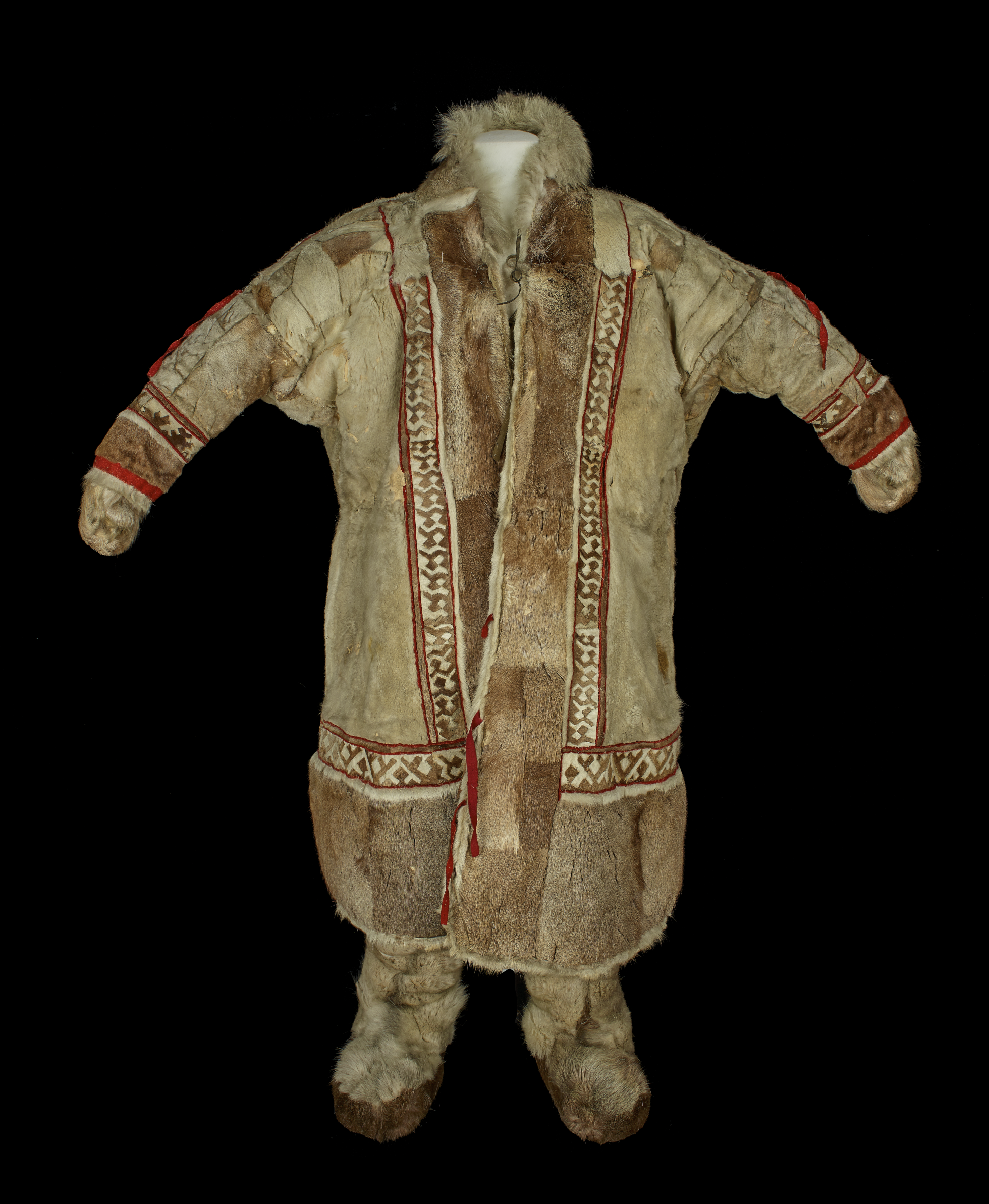 Photograph of a man's coat;. The coat is calf-length, slightly flared in shape, and made from many pieces of bear fur. The fur is cream and mid-brown in colour. It has a fur collar. Mittens poke out from sleeve ends. Strips of geometric patchwork (cream and brown fur) are stitched either side of the entre front opening, above hemline, and near sleeve ends. It is edged with red tabby woollen cloth.