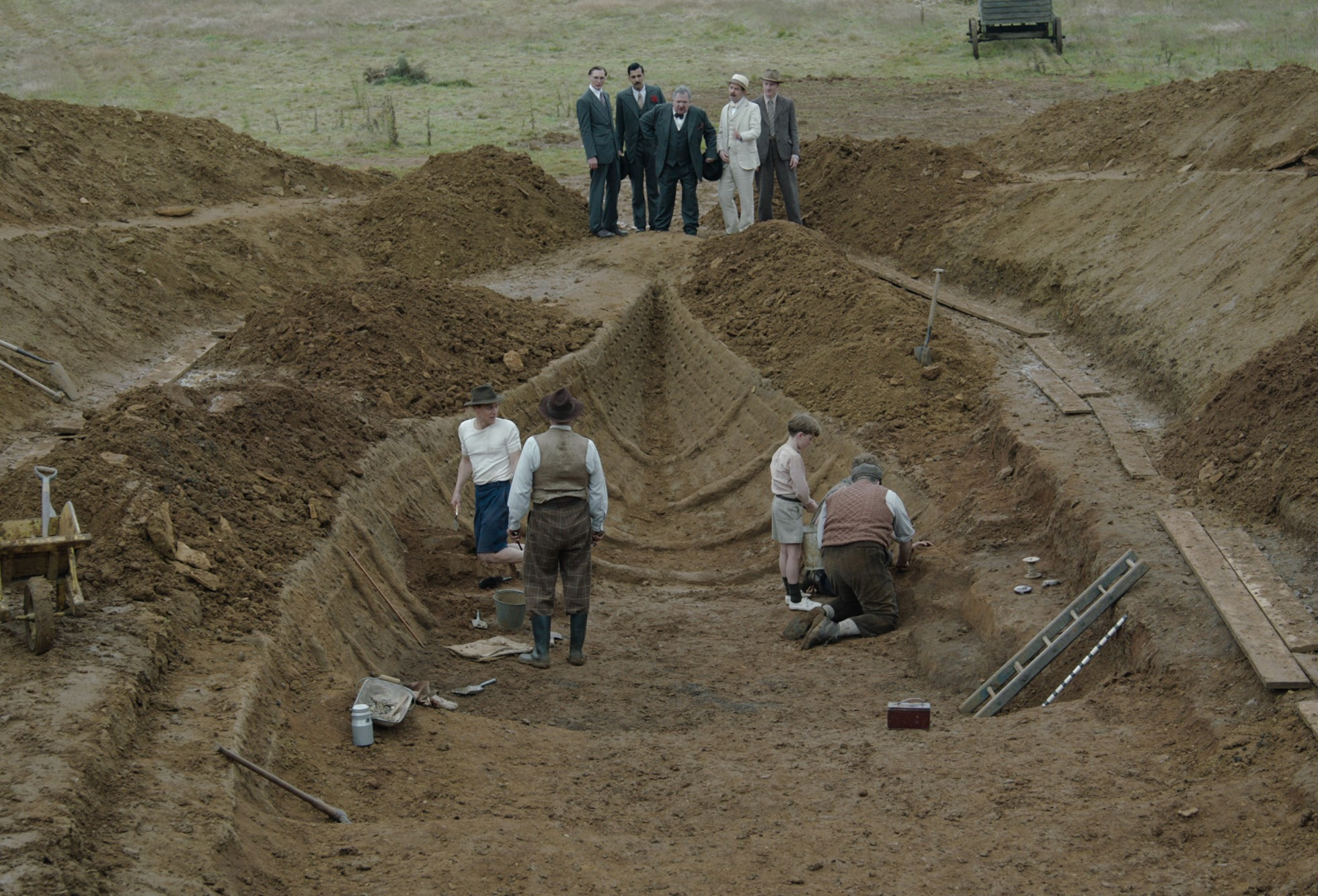 Three men and a child work in the trench, They are watched by 5 men, all wearing suits who stand at the end of the trench. There are piles of soil on the banks of the trench.