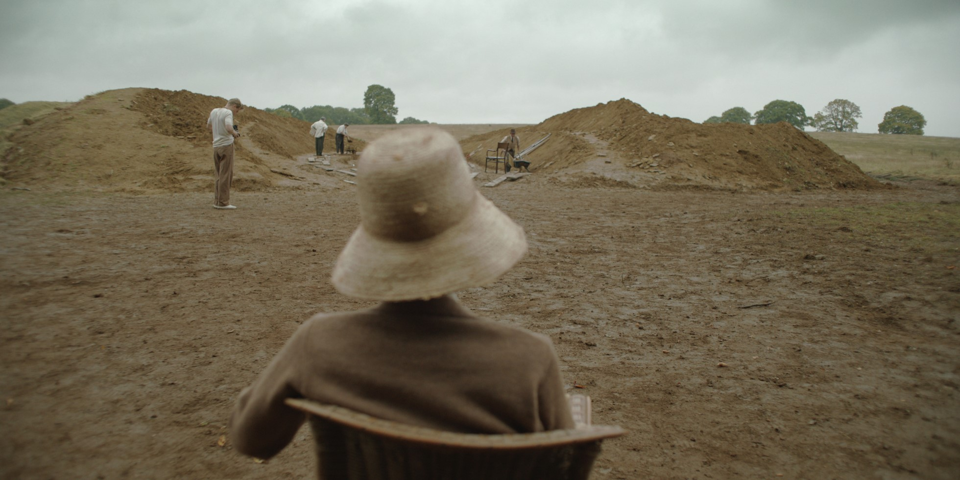 Still from the film showing Carey Mulligan as Edith Pretty. She is shot from behind sitting in a seat. She is wearing a brown jacket and straw hat. She is observing excavations in the background, where several men are seen amongst piles of soil.