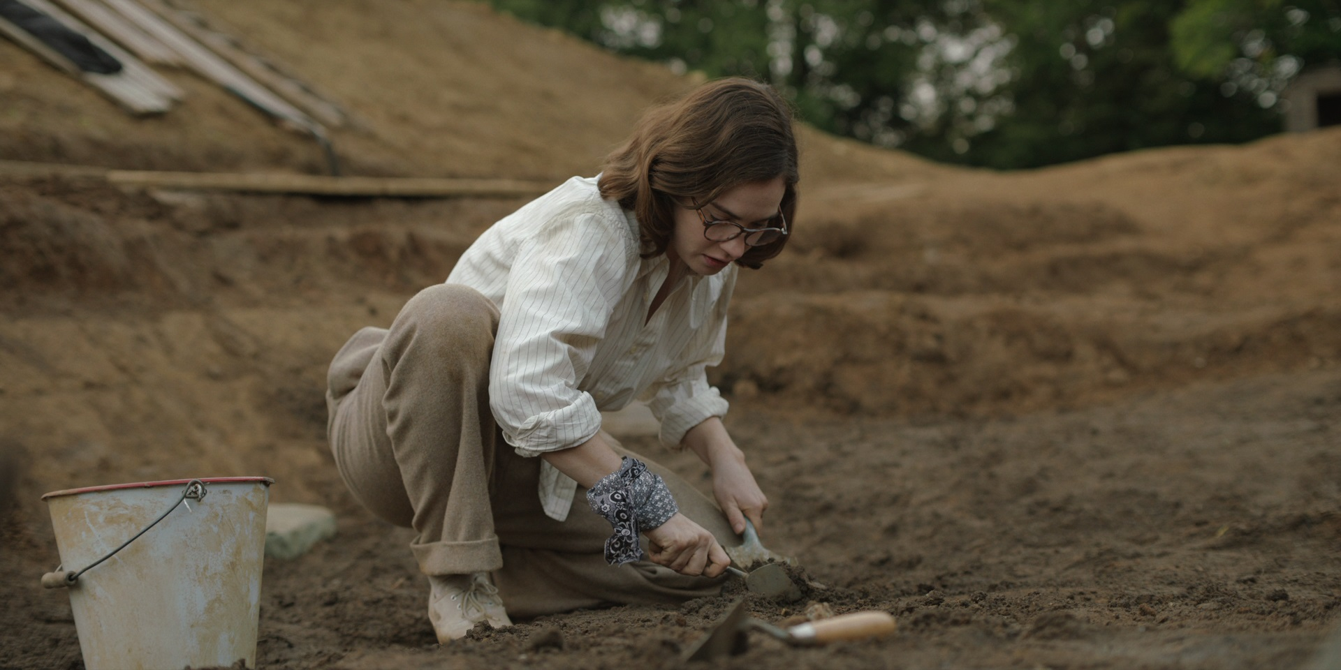 Still from the film of Lily James as Peggy Piggot excavating. She wears  a white shirt, brown trousers and white pilmsolls. She holds a trowel  and has a metal bucket next to her.
