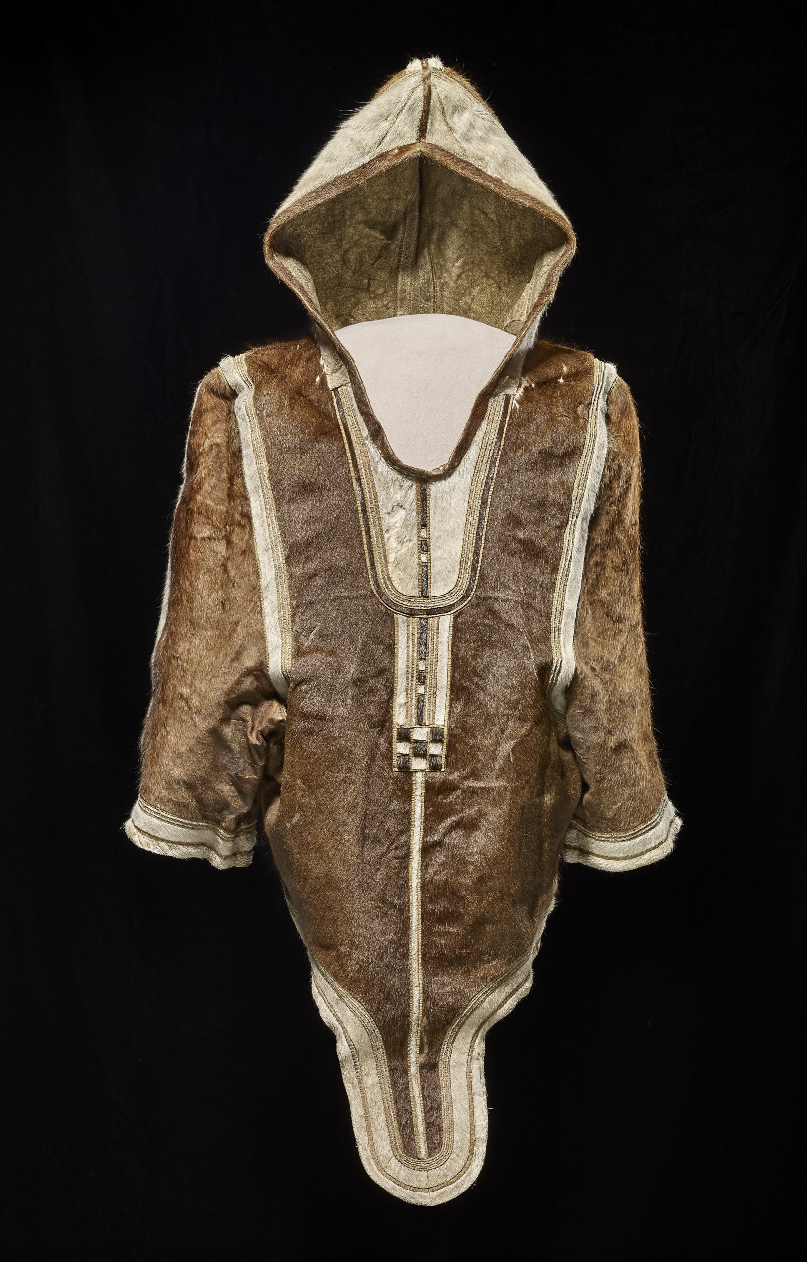 Photograph of a parka, made of brown and white caribou skin. The parka is mostly brown with white trim, and a white hood.