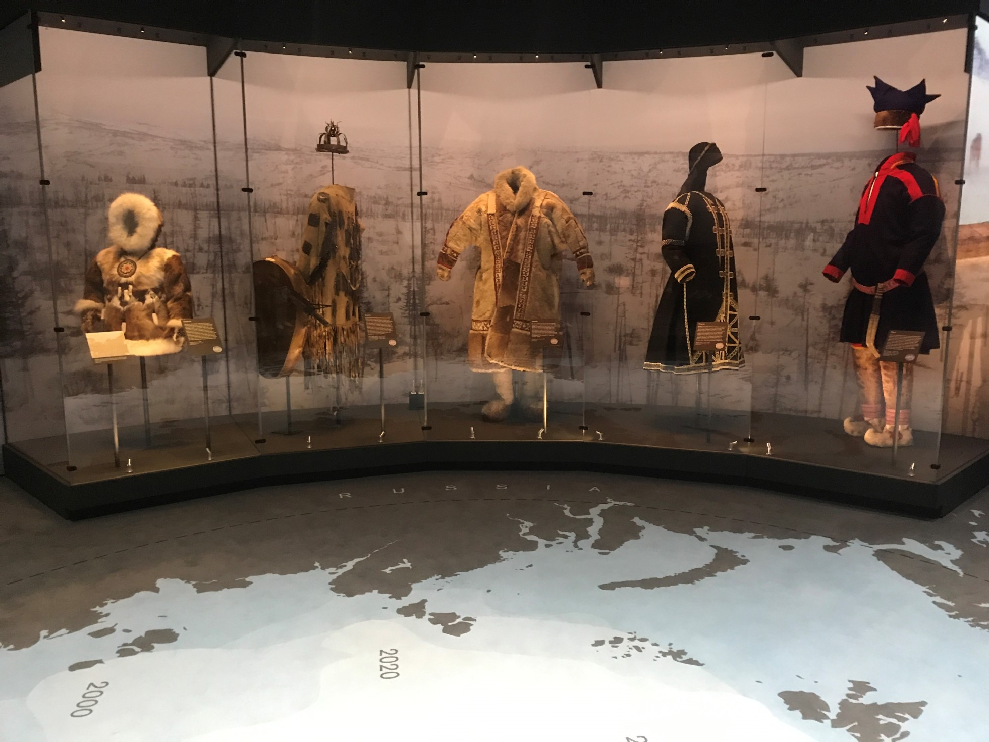 A photograph of five different Arctic outfits on display in the Arctic exhibition. The display includes parkas. On the floor is a map of the Arctic.