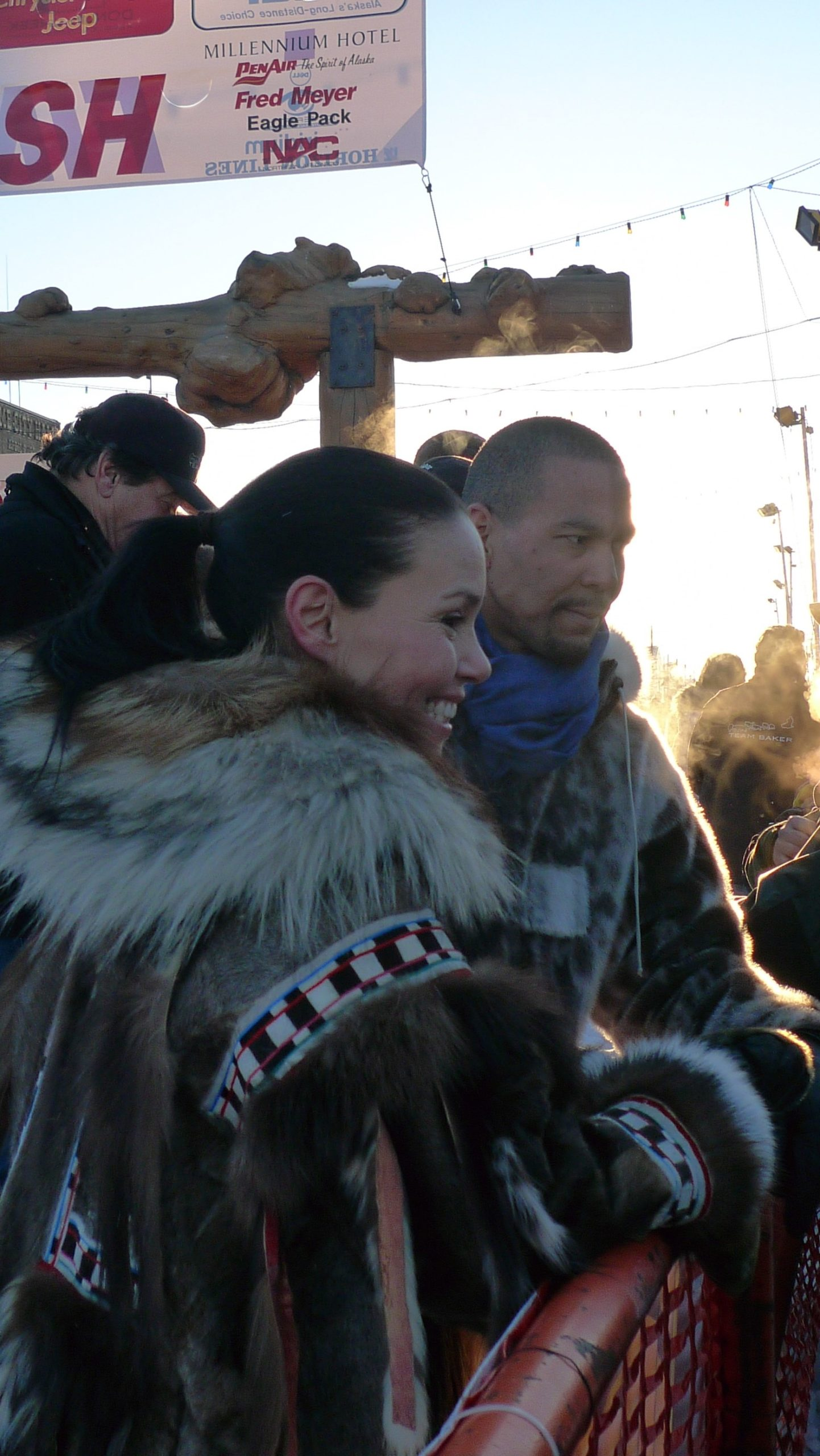 Photograph of a woman shown in profile. She leans against a red metal railing and looks to the right. She is smiling. She wears an elaborate parka with black and white trimming.