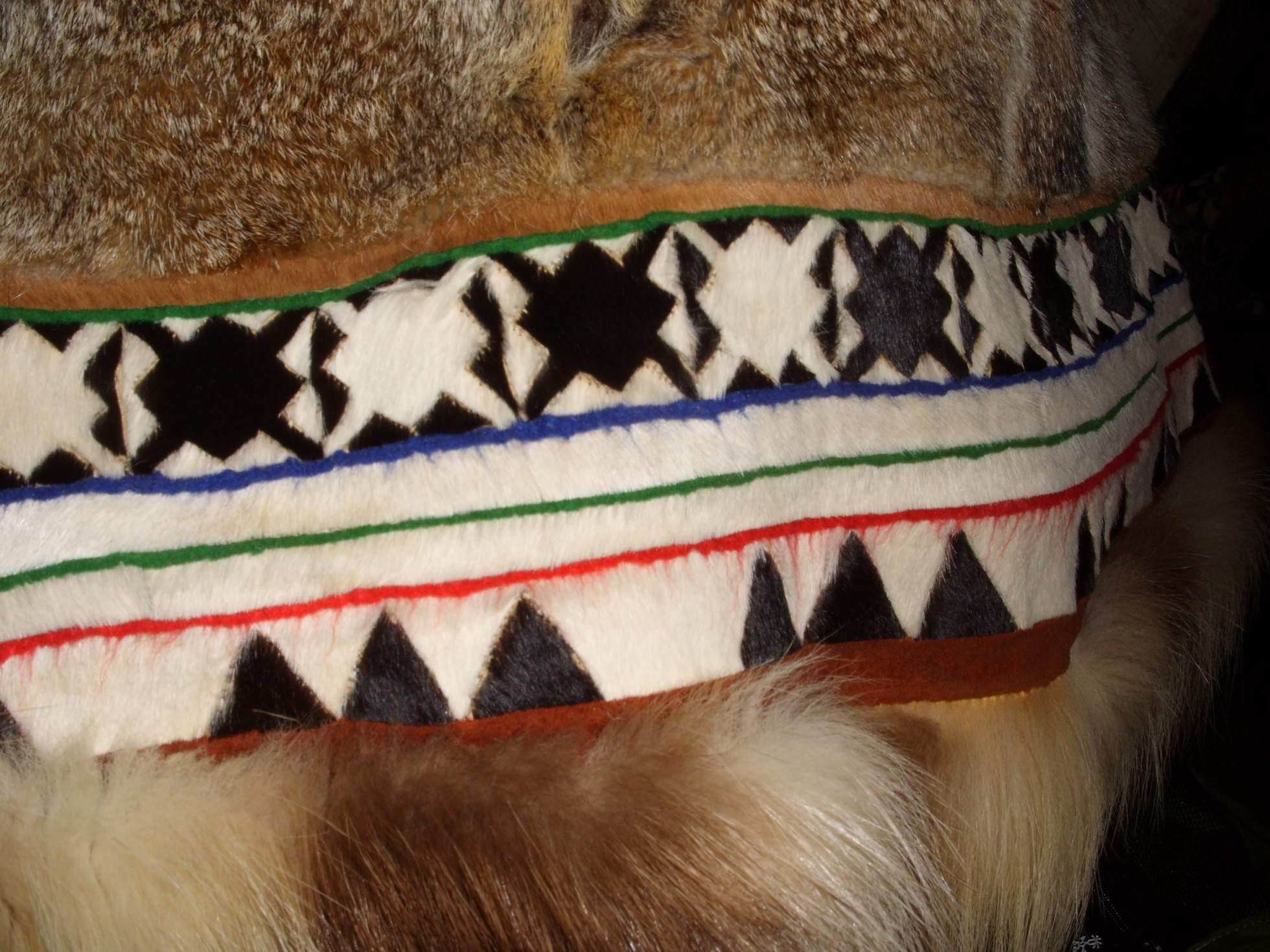 Detail of a parka trim in black and white. The motif is of triangle and star shapes. There are thin horizonal lines of blue, green and red.