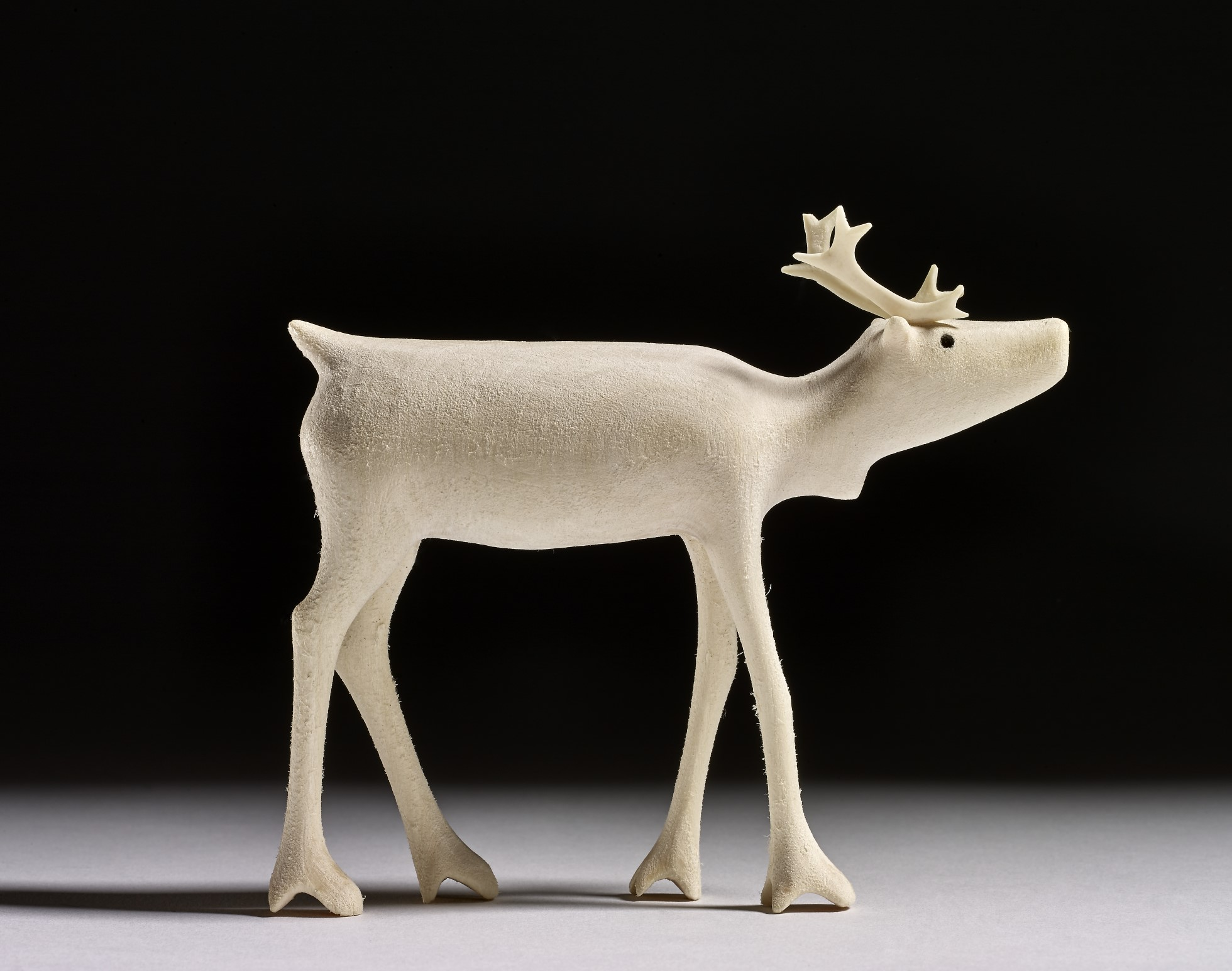 Finely carved and sanded figure of a caribou, cut from wood. The eyes are marked with drilled or punched shallow holes, then blackened. The antlers are made of delicately carved bone.