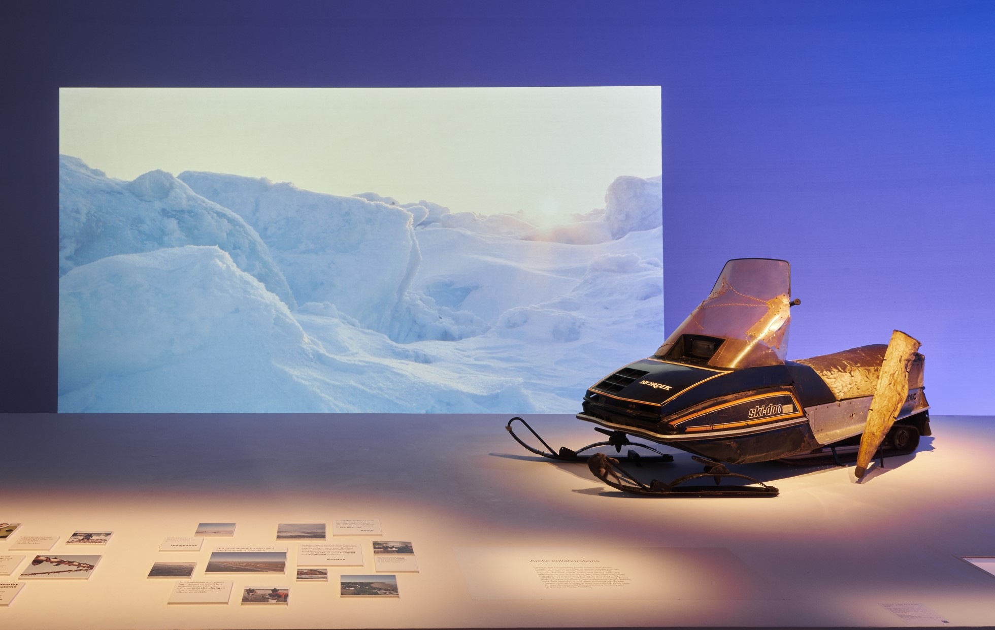 Photograph of a snow mobile on a platform inside the exhibition. Behind is a screen showing an image of a snowy landscape in the Arctic. There is dramatic lighting with a purple colour on the back wall.