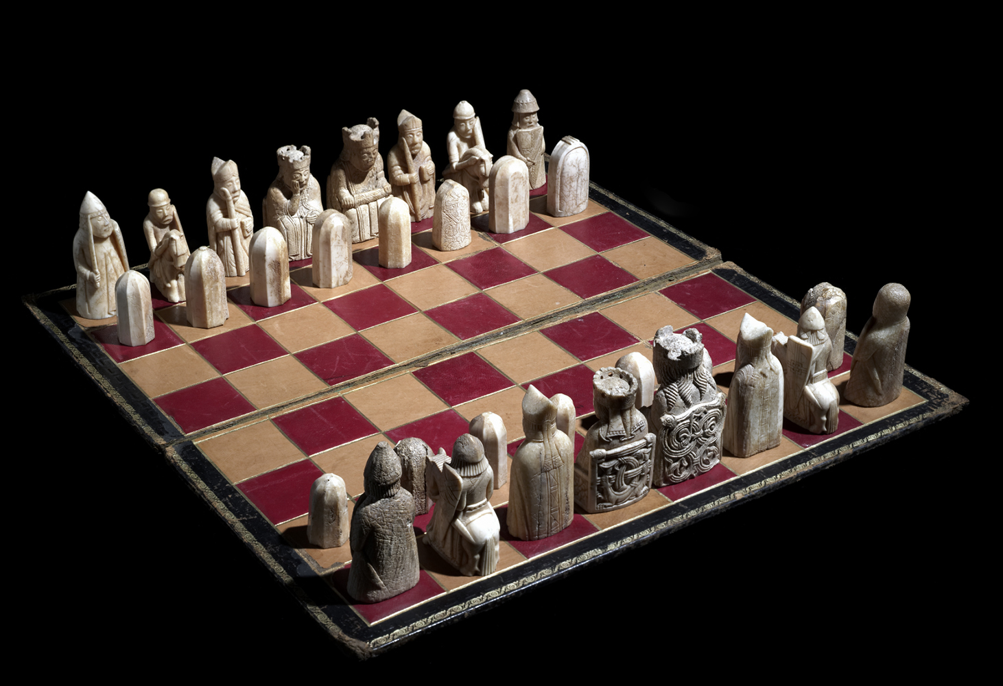 A photo of the Lewis Chessmen from above, showing the chess pieces standing on a red and cream chess board.