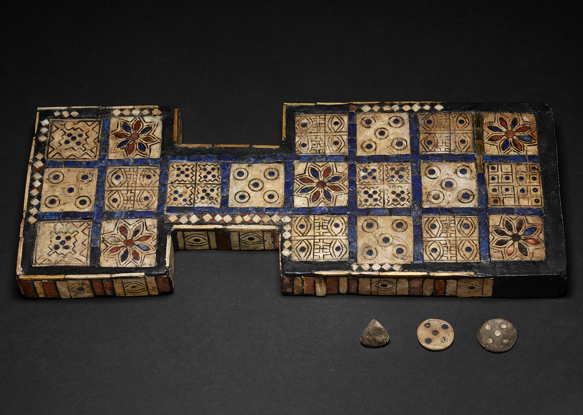 The Royal Game of Ur photographed from above, inlaid with wood and shell, coloured with red and blue patterns.