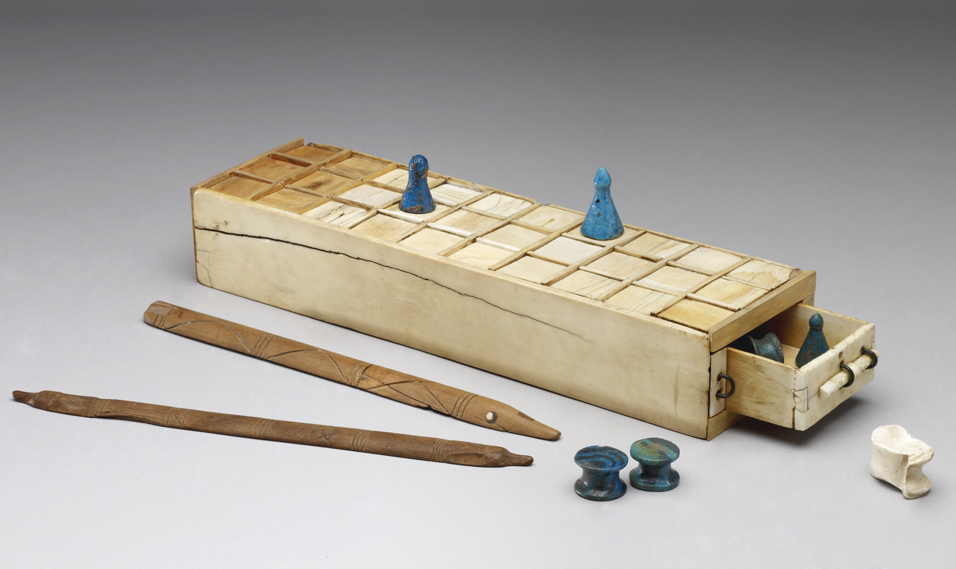 A cream coloured box, with a draw containing gaming pieces, and a grid of 30 squares on the top.