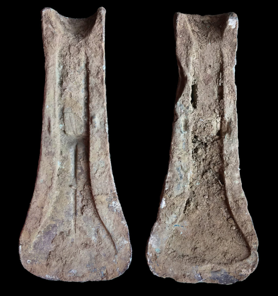 Two halves of a bronze axe-head mould, heavily corroded.