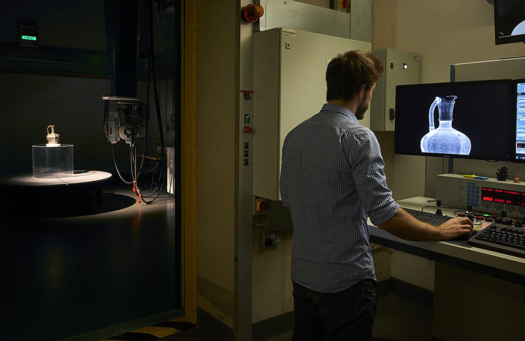 A photograph of scientist Dan O'Flynn working at a computer screen in the X-ray lab. To the left, the door to the chamber is open and a ewer is seen under dramatic lighting.