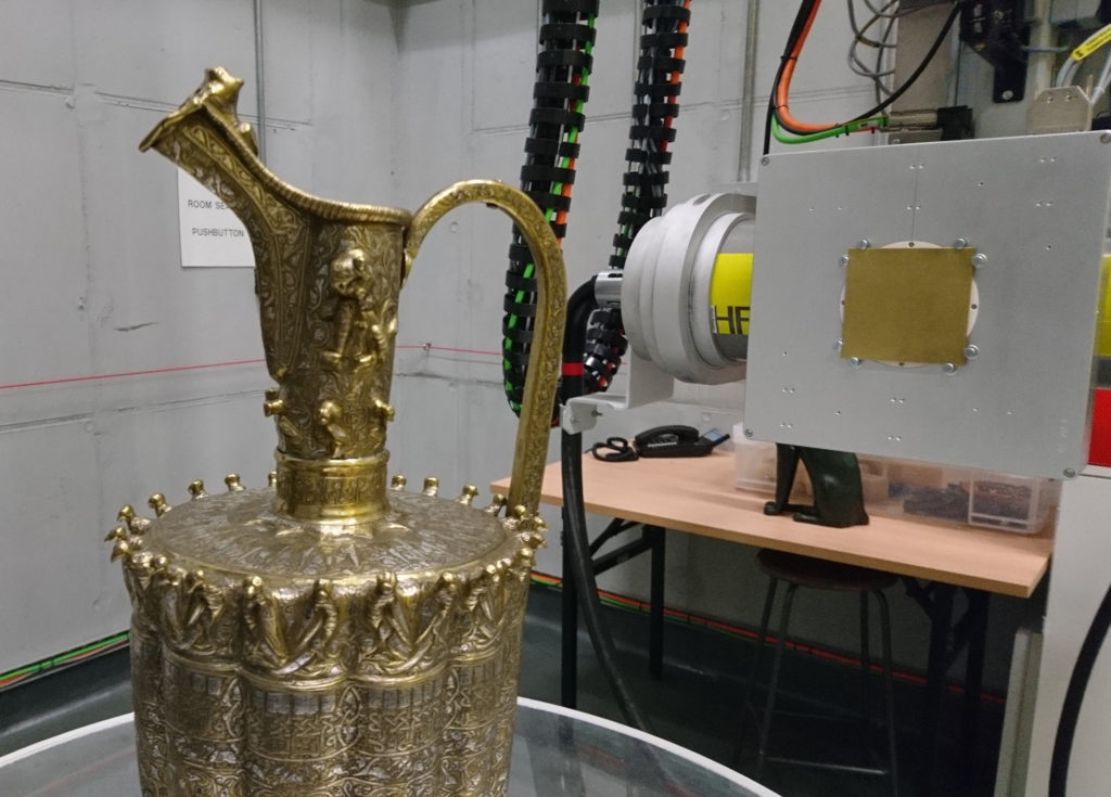 A photo of the top half of the brass ewer, shown in front of X-ray equipment.