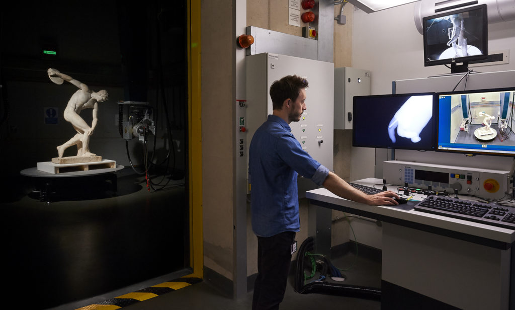 Scientist Dan O'Flynn working in front of three computer screens in the X-ray lab. To the left, the Discobolus statue can be seen in the chamber under dramatic lighting.