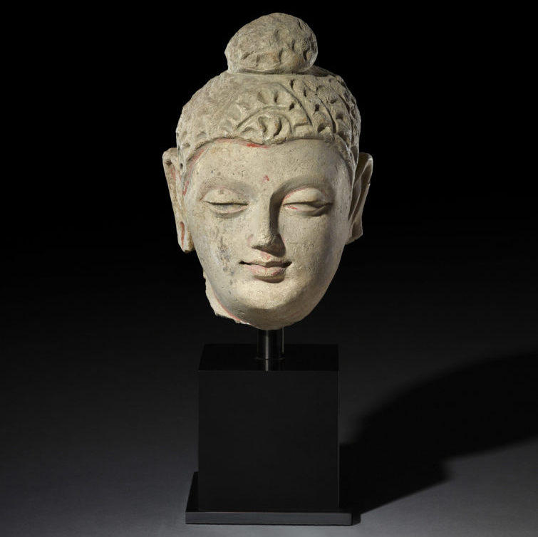 A clay head of the female bodhisattva wearing a crown. There are traces of red paint on the face including the eyelids, the forehead and above the lips.