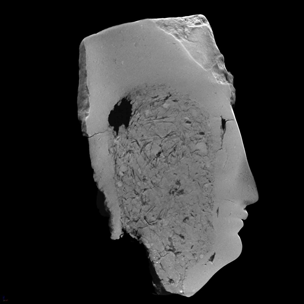 An X-ray CT scan showing a cross-section of a clay head. The black-and-white image shows a solid white outline of the head and facial features, and the inside shows a rougher texture.