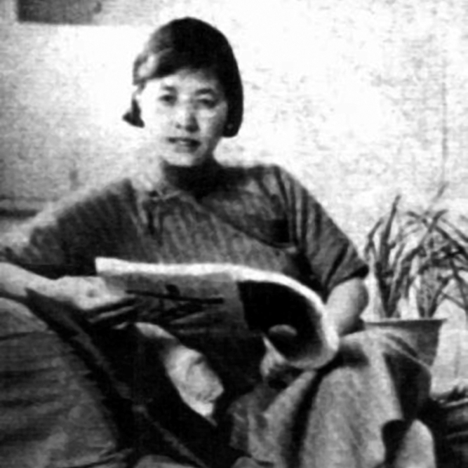 A black and white photo of a woman sitting on a chair, reading a magazine and wearing a striped dress. A plant is behind her on the right.