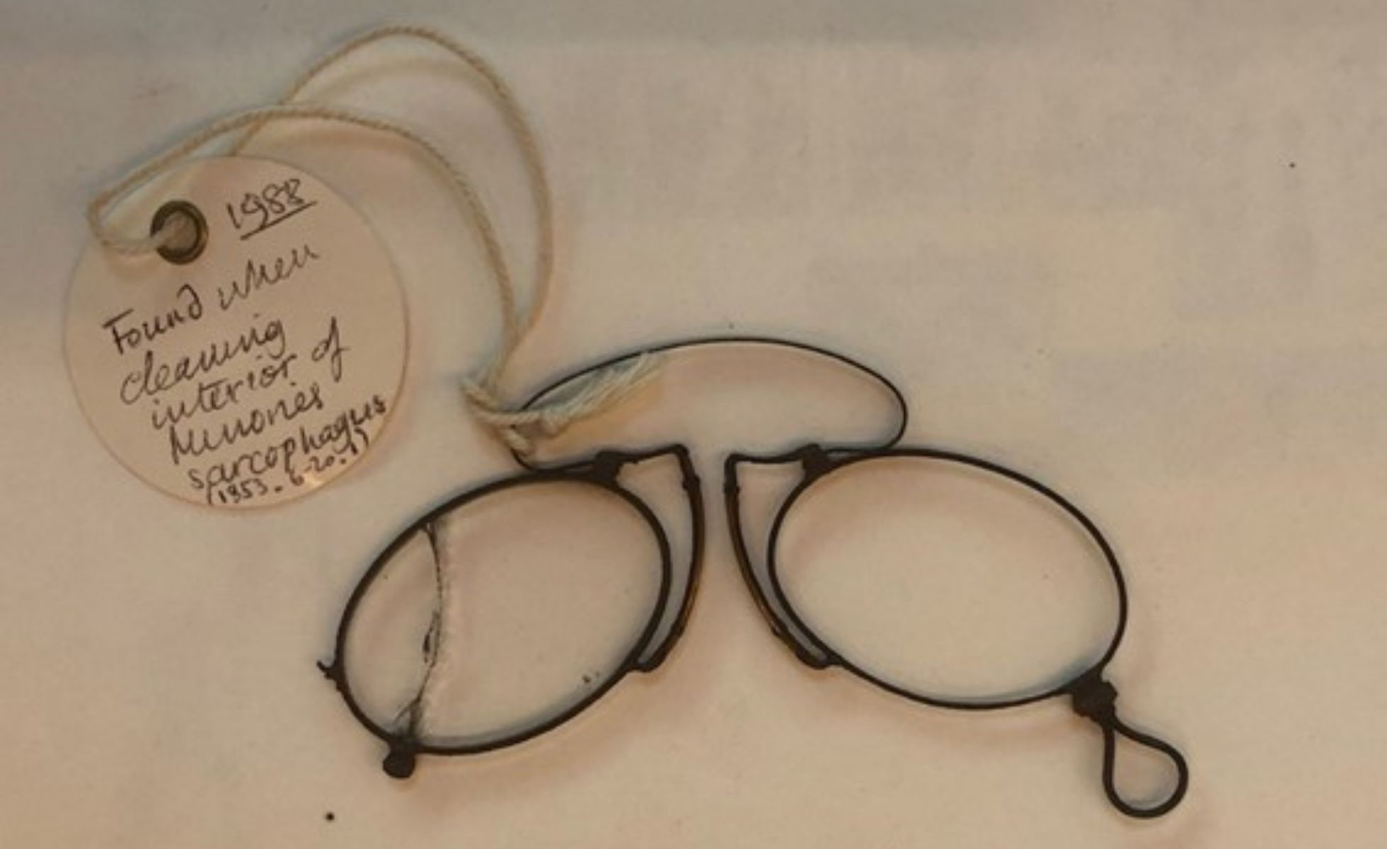 Photograph showing wire spectacles with a tag attached