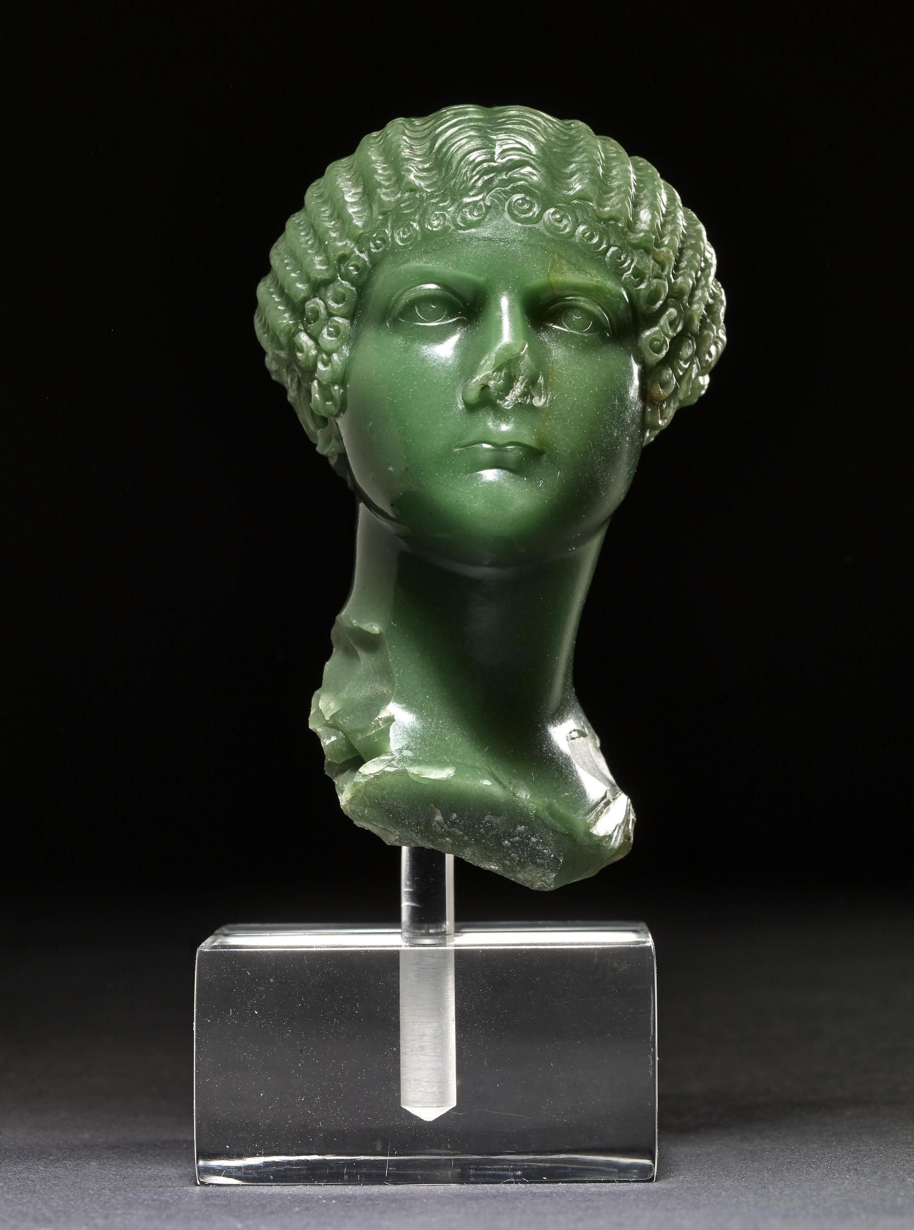 Green chalcedony cameo portrait bust of the younger Agrippina. The cameo is broken off at the base of the neck and at the lower nose.  Part of the empress's tunic survives at the right lower edge. The hair is parted centrally and brushed to either side of the head in a series of increasingly tight waves. Around the face is a row of tight snail-shaped curls; above the ears these are arranged in two tiers.  The face is full, with a prominent squarish jawbone. The eyes are set wide apart beneath a low brow; the eyebrows are not indicated. The mouth is small and the expression sullen.