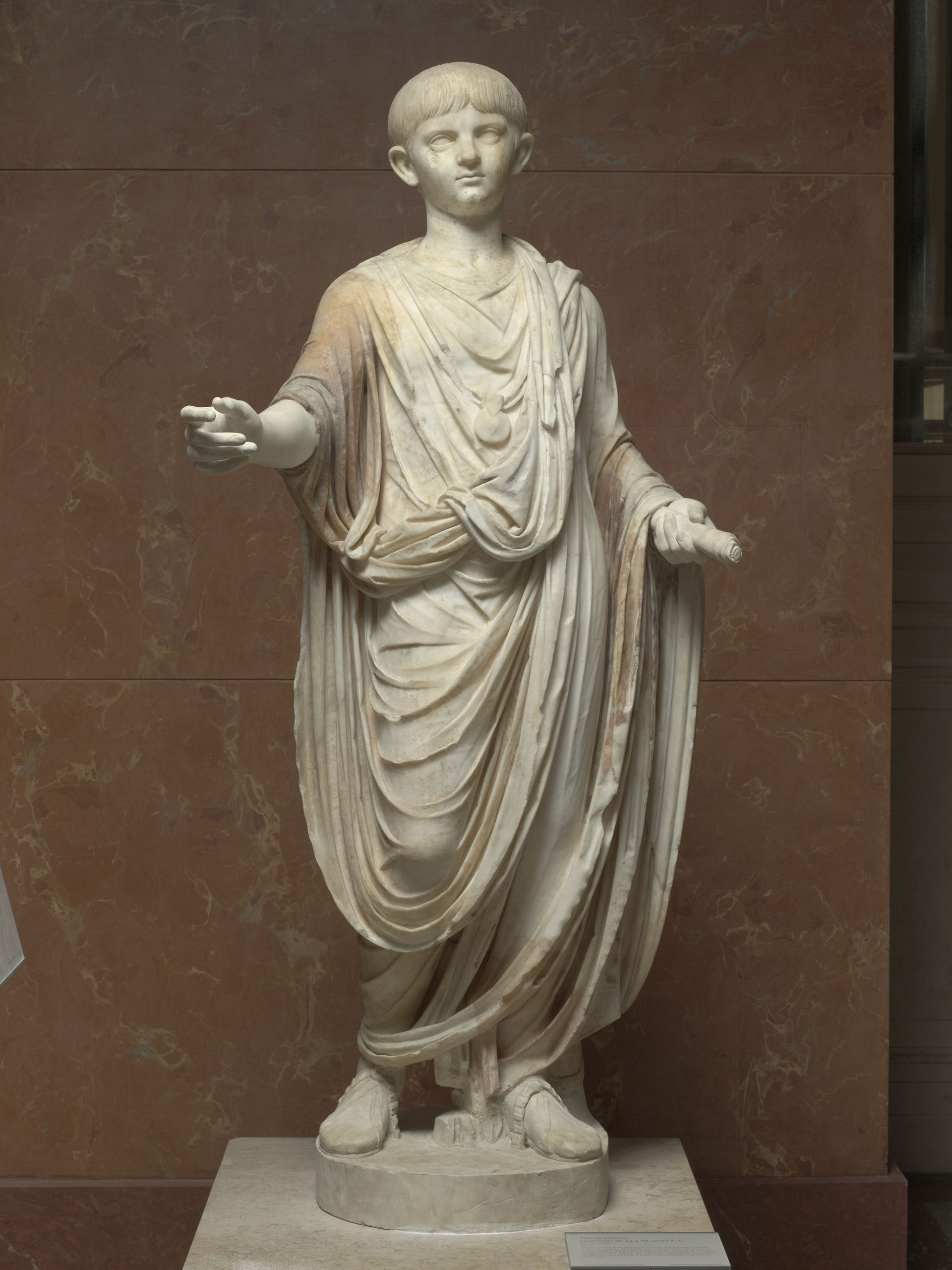 A cream coloured statue of a young Nero wearing a large toga, against a red marble wall.