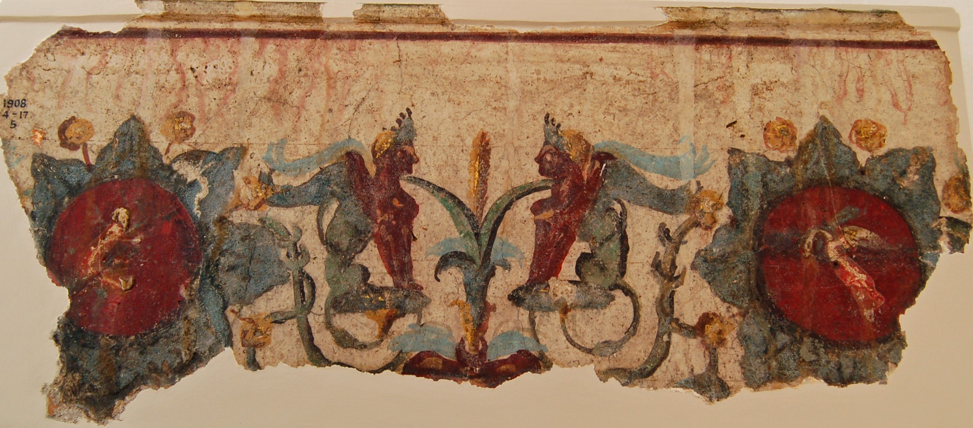 Fragment of a gilded wall painting in red, turquoise and gold. Part of a frieze showing a pair of sphinxes amongst acanthus plants with large flowers.