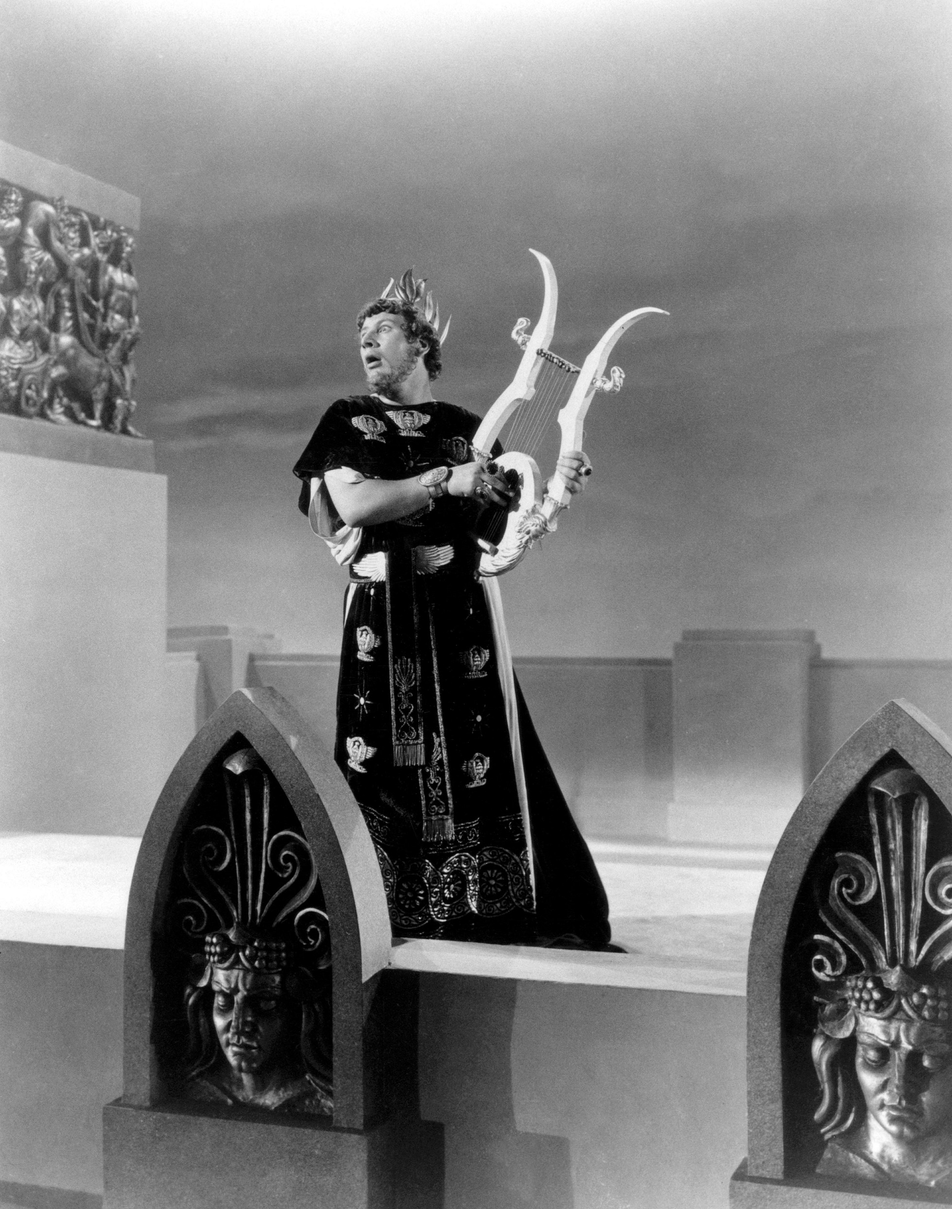 Black and white still from a film. Nero played by Peter Ustinov stands on a roof terrace wearing a long robe and crown. He plays the lyre and looks out, presumably over burning Rome, though the city cannot be seen.