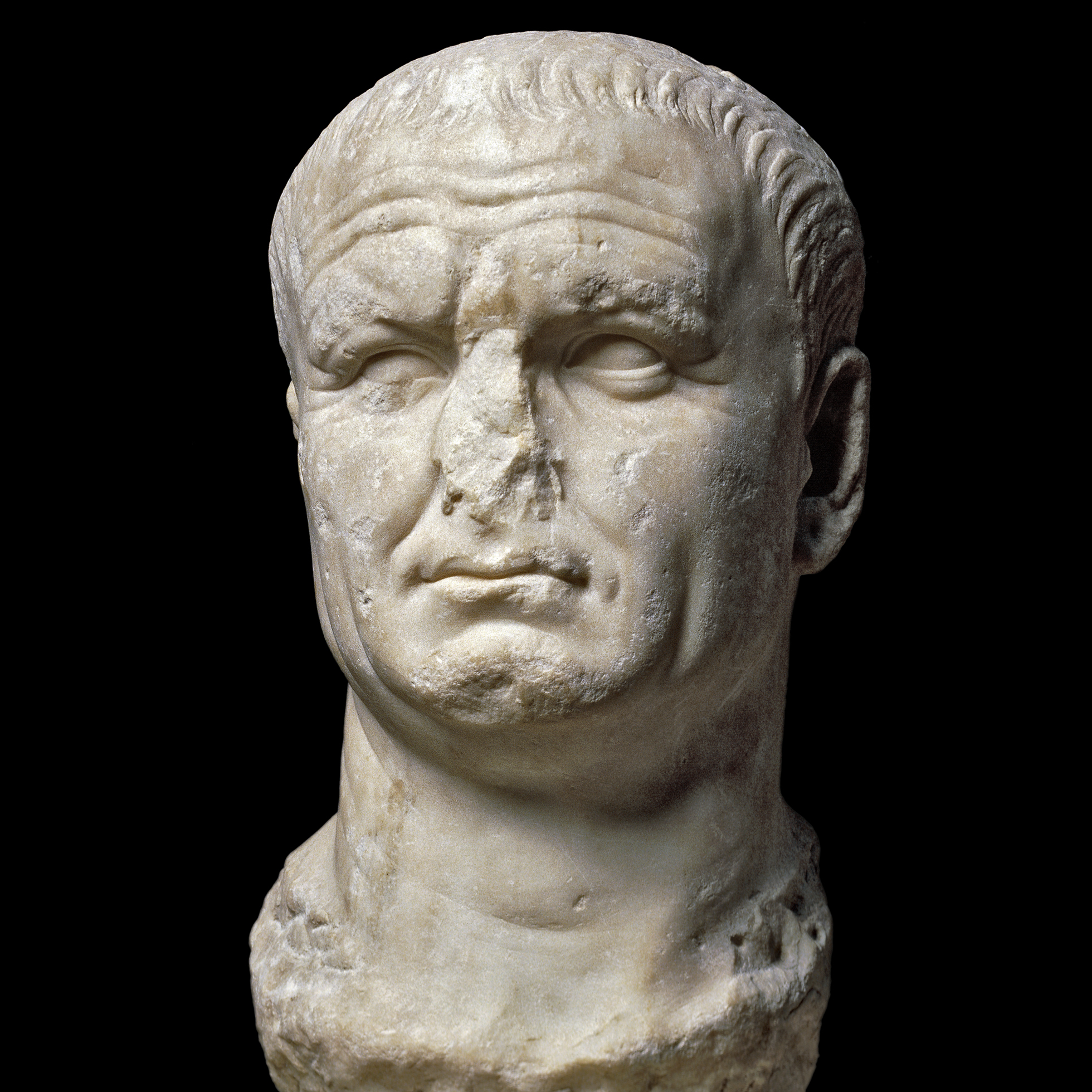 A cream coloured marble bust of the emperor Vespasian, with deeply set forehead wrinkles, short hair, and a missing nose.